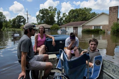 John Booth, left, sits with Angela Latiolais's family while helping them save belongings after flooding in Gonzales, La., on Aug. 16, 2016.