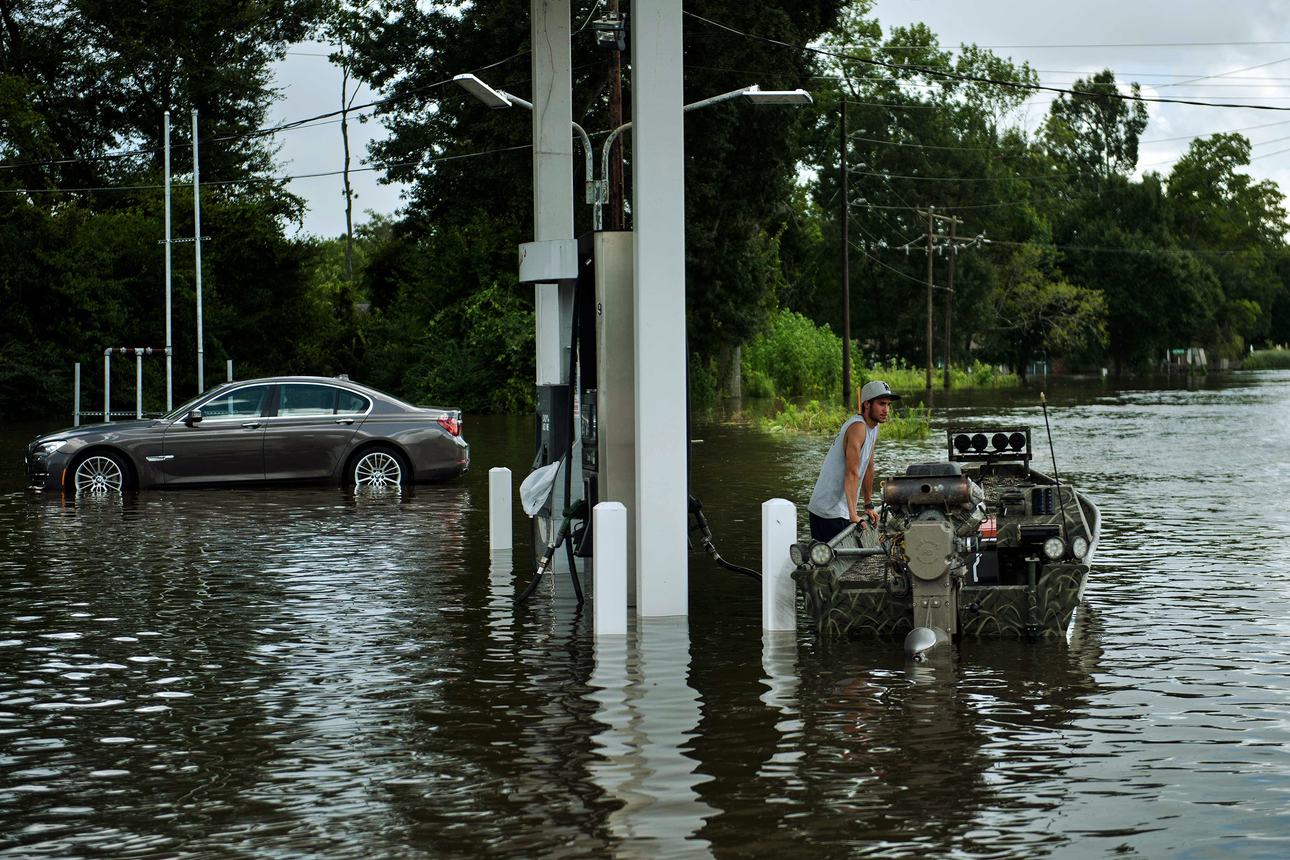 A man waits at a gas station with a boat while helping to evacuate a neighborhood after flooding in Gonzales, La., on Aug. 16, 2016.