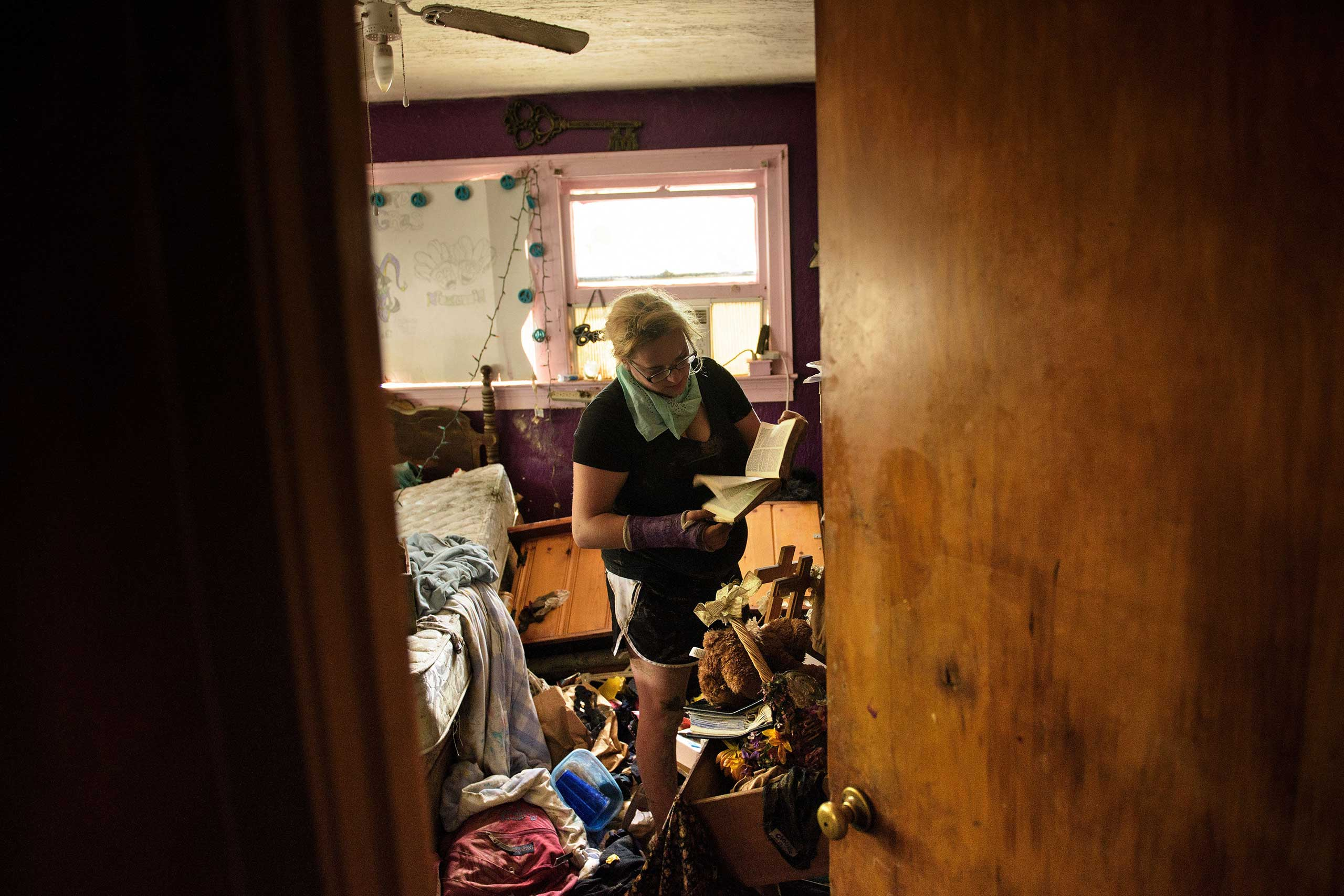 Cheyenne Hughes looks at a bible while salvaging items in her family's home after flooding in Denham, La., on Aug. 17, 2016.