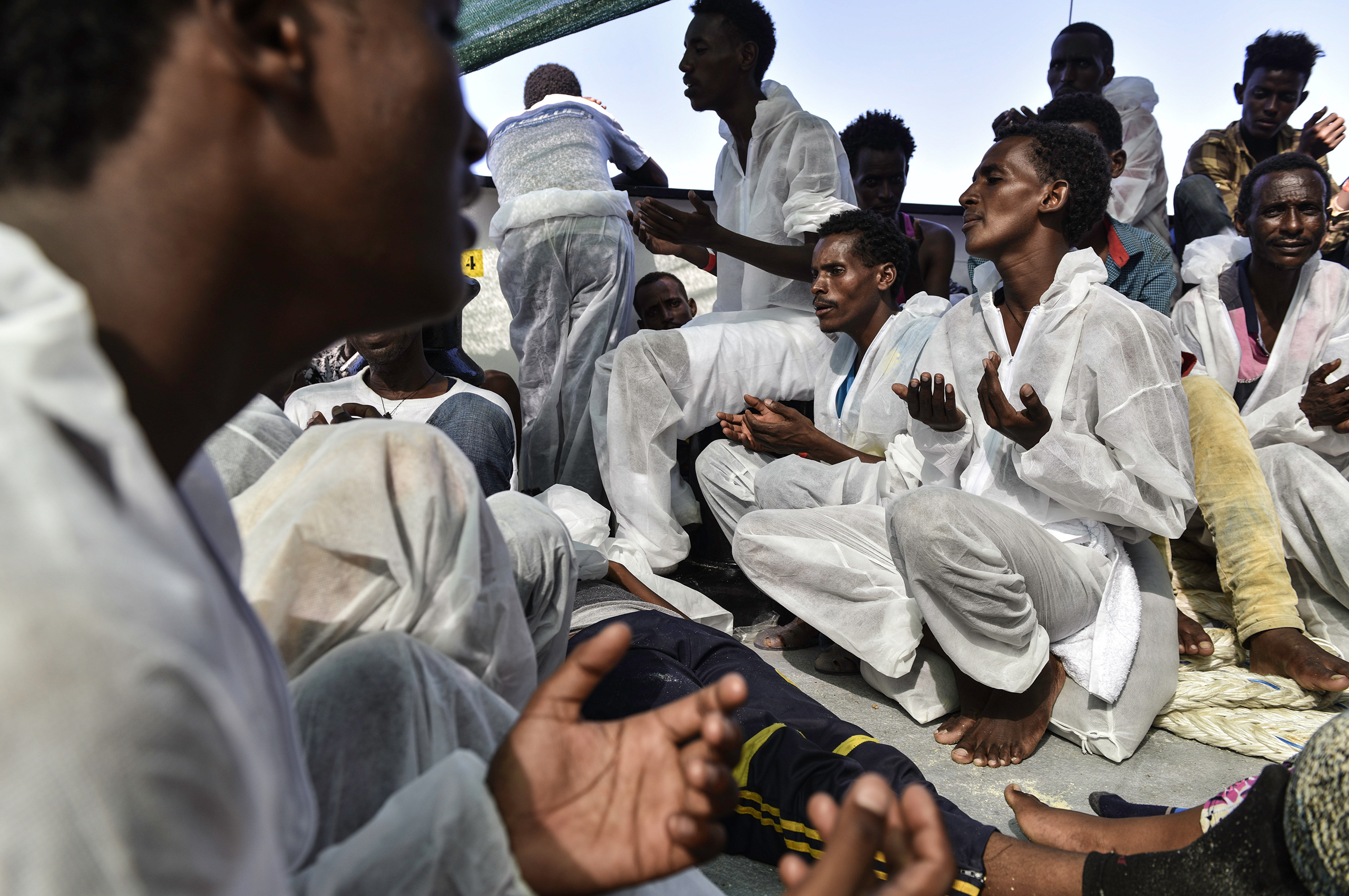 Eritrean Orthodox Christian men sing and pray after their rescue, Aug. 21, 2016.