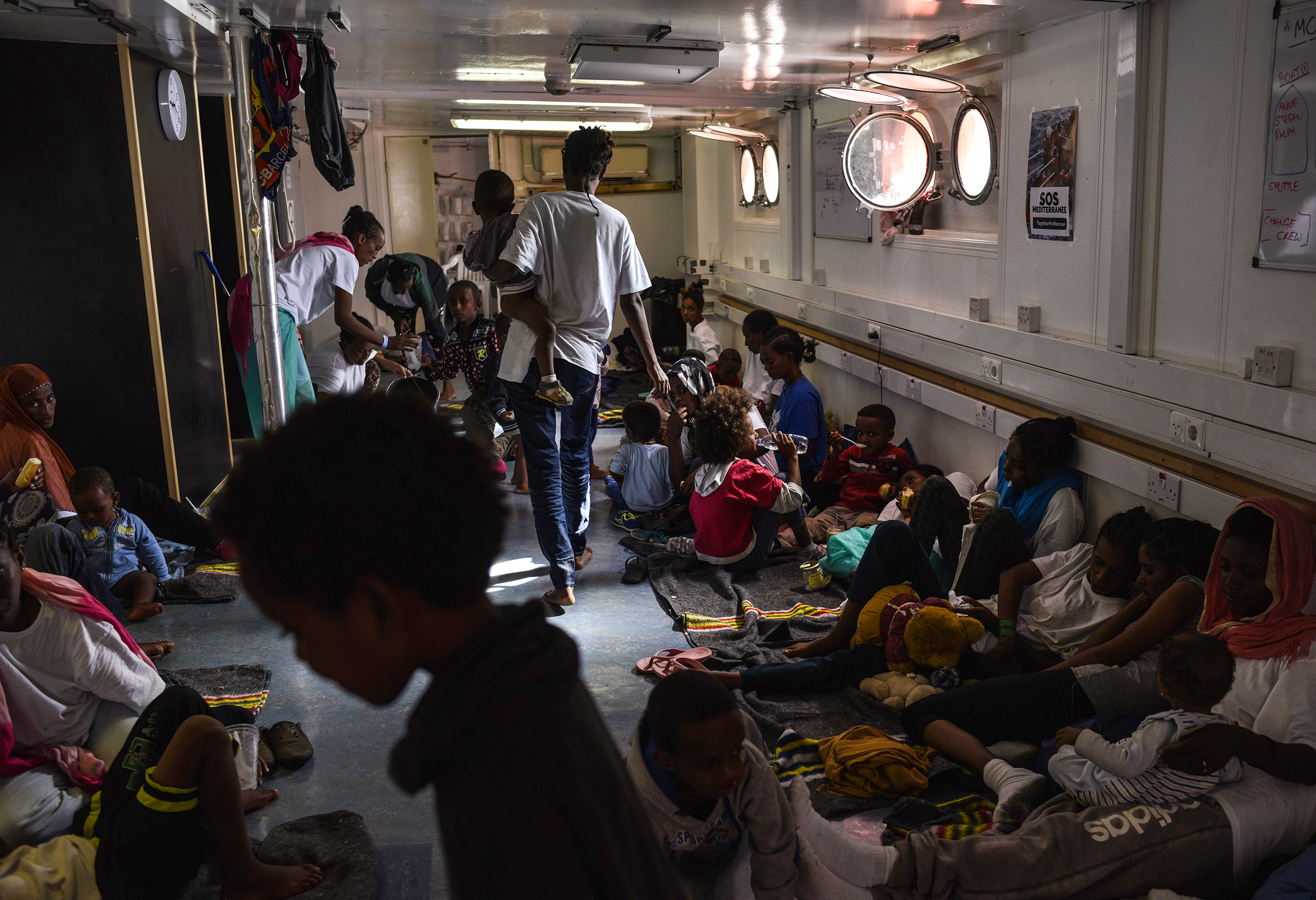 Women and children eat and rest below the deck of the rescue ship. Aug. 22, 2016.