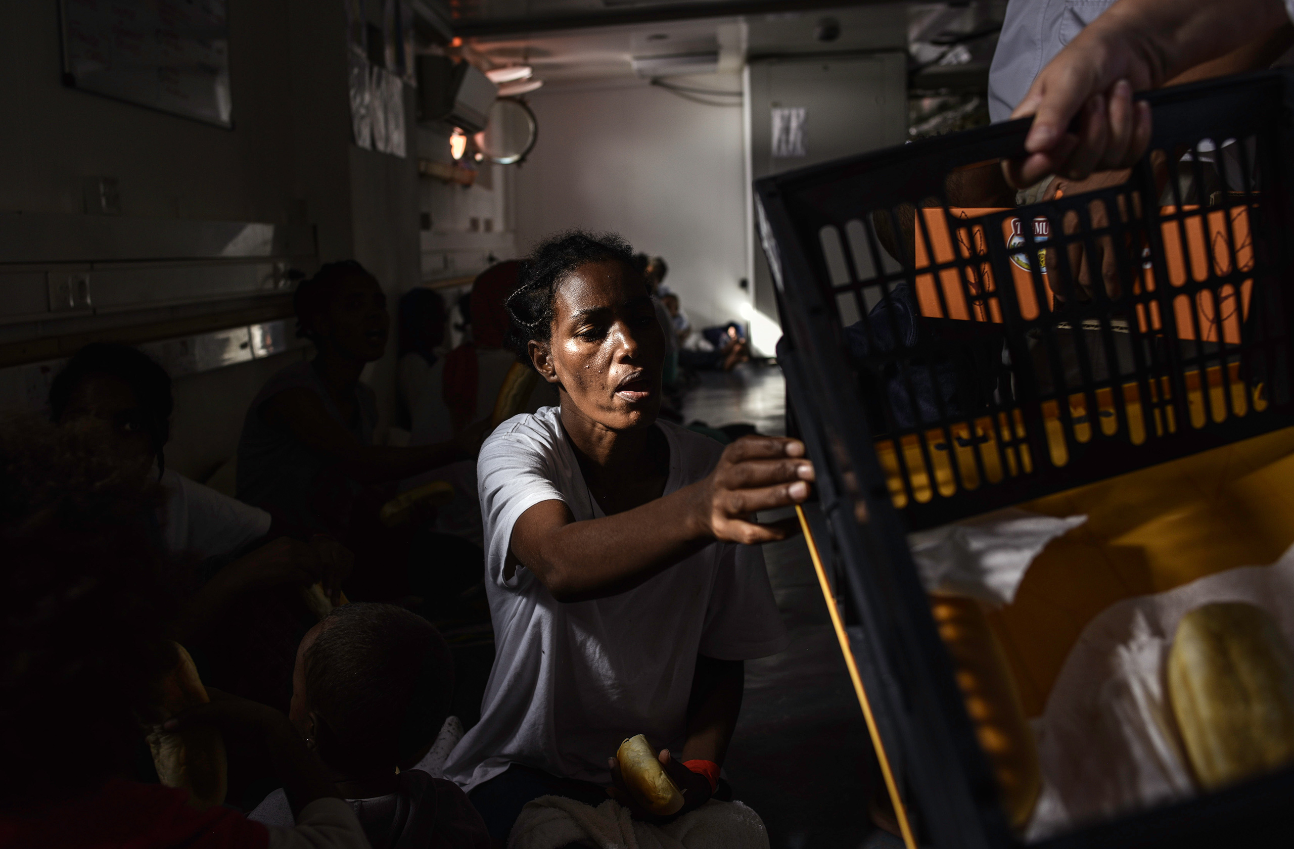 A hungry Eritrean woman reaches for bread at breakfast, the morning after being rescued Aug. 22, 2016.
