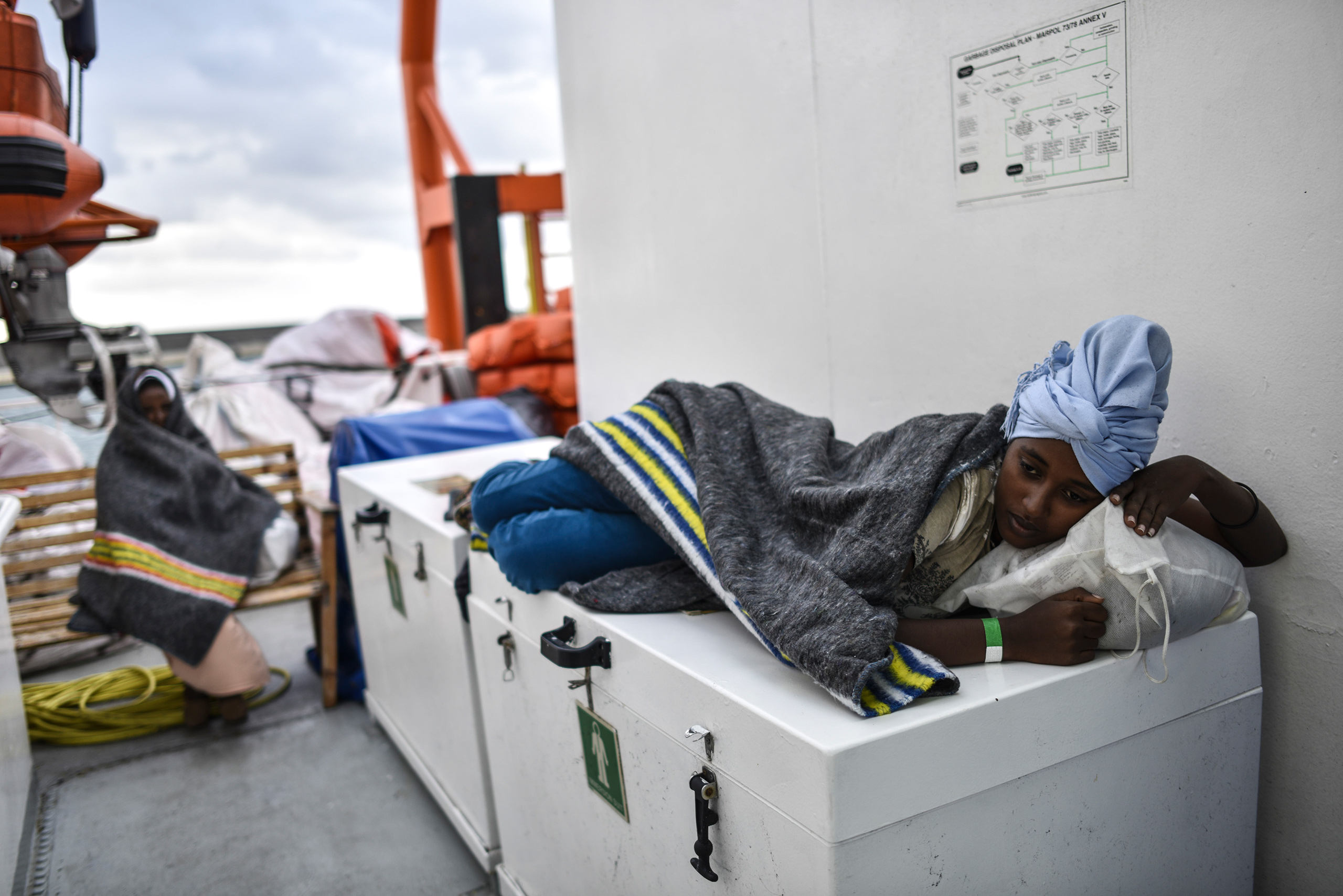 A young migrant woman rests on the deck as the ship sails to Italy, Aug. 23, 2016.
