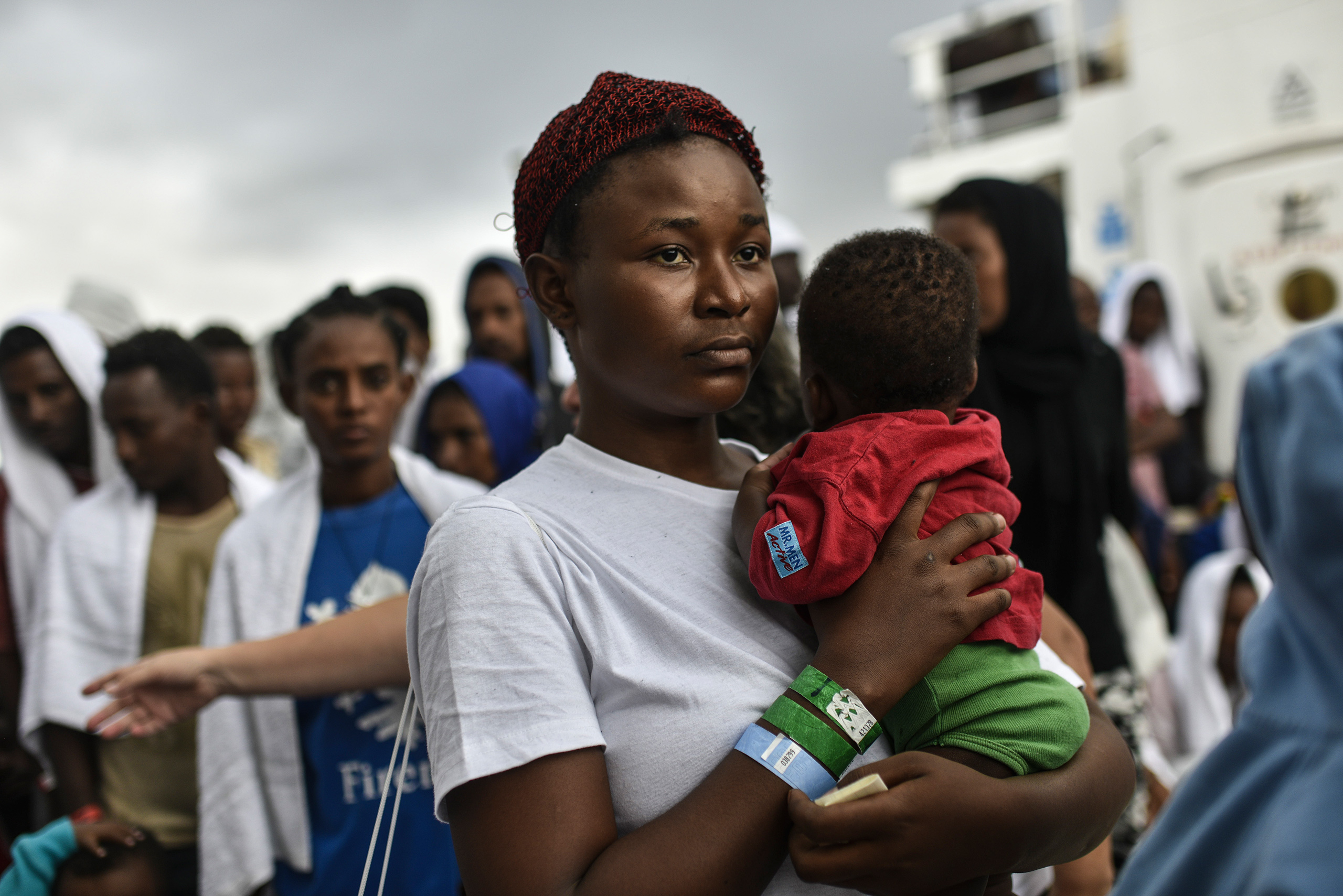 A Nigerian migrant, Goodness, age 20, holds her young daughter Destiny, as she waits to disembark at the Catania port, Sicily, Aug. 23, 2016.