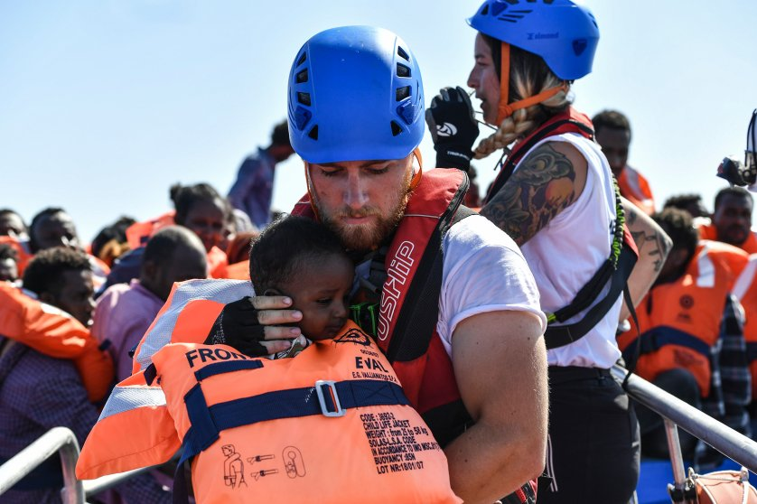 A rescue worker cradles a young child to safety, Aug. 21, 2016.