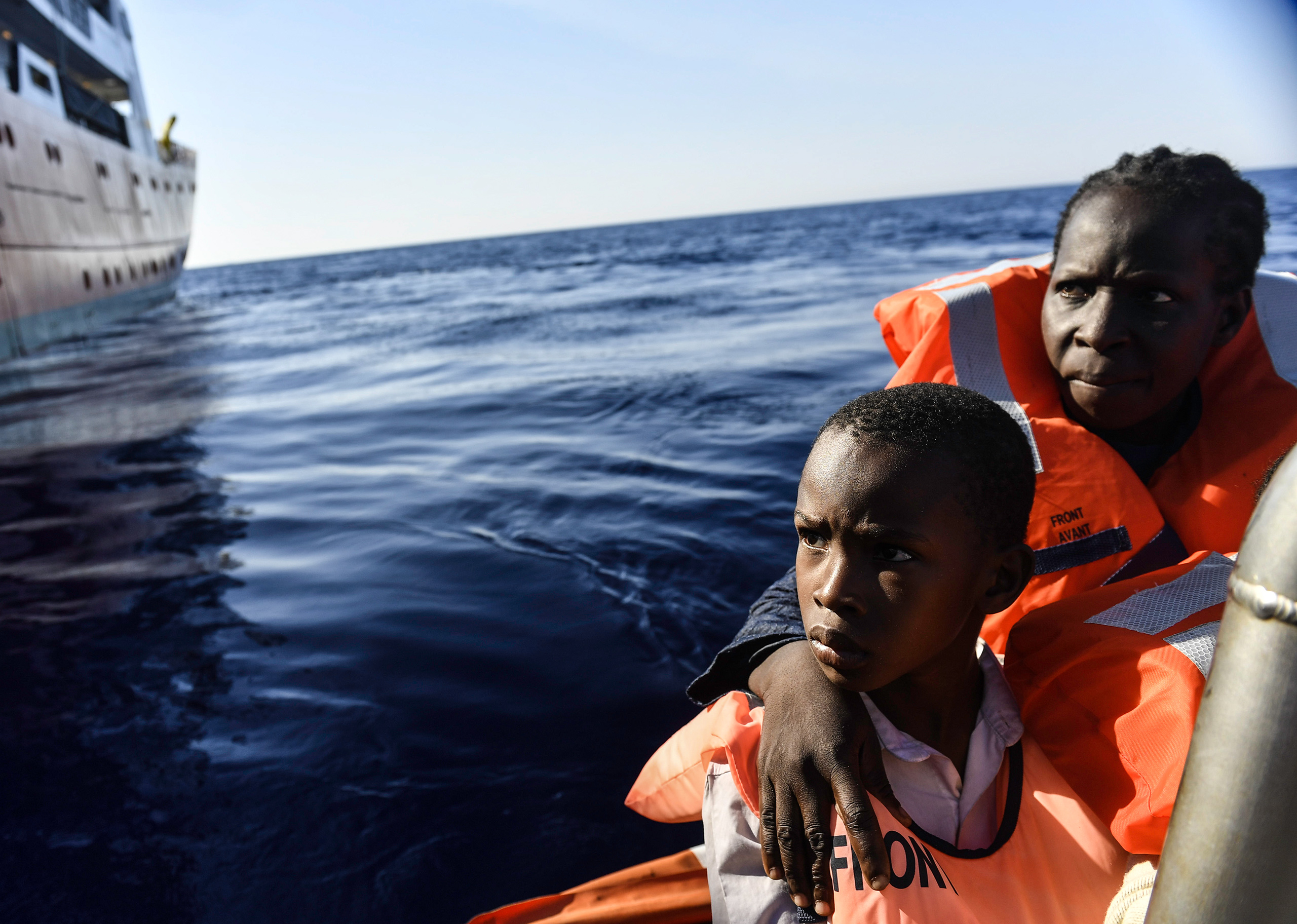 Victoria, a 42-year-old Nigerian migrant and her son Victor are transferred to the MV Aquarius, minutes after they were rescued with more than 130 others on a rubber boat in the Mediterranean, Aug. 20, 2016.