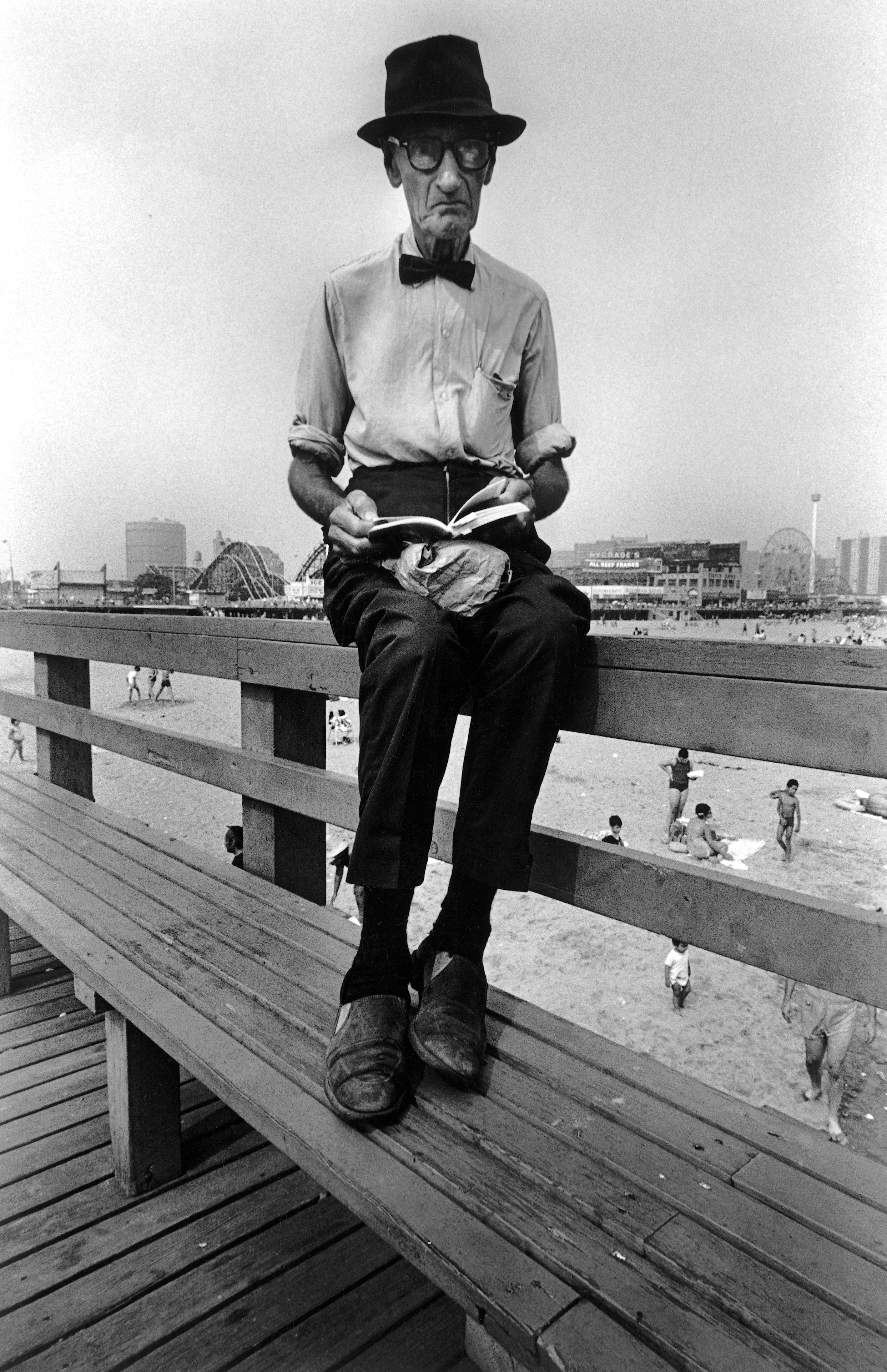 Man wearing bow tie, 1970. This photo was taken on the pier of the Coney Island Beach in Brooklyn during the summer of 1970. For me while it's quite graphic with the older man sitting against the sky, I think it shows a disappearing way of life, a man dressed with bow tie and long sleeved white shirt reading a book, with lunch on his lap, in the middle of summer at the beach. He's out of step with the people enjoying the beach below.