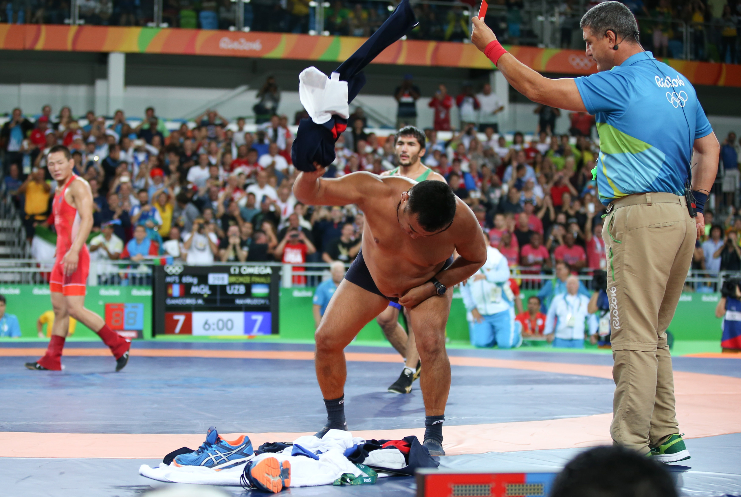 The coach of Mongolian wrestler Ganzorigiin Mandakhnaran takes off his clothes as he protests after the men's freestyle 65-kg bronze-medal match against Ikhtiyor Navruzov of Uzbekistan at the Olympic Games on Aug. 21, 2016