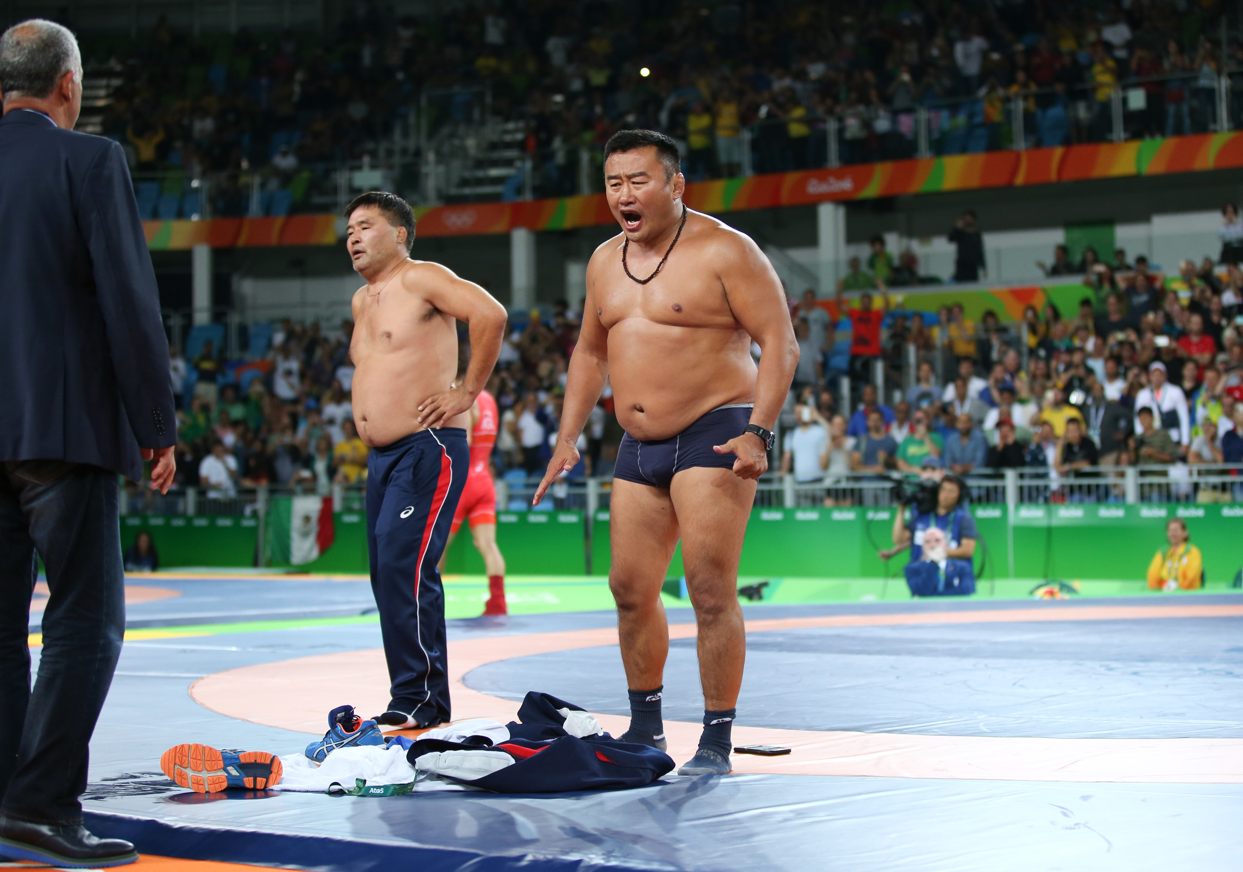 The coach of Mandakhnaran Ganzorig of Mongolia takes off his clothes as he protests after the Men's Freestyle 65 kg Bronze final against Ikhtiyor Navruzov of Uzbekistan at the 2016 Rio Olympics on Aug. 21, 2016.
