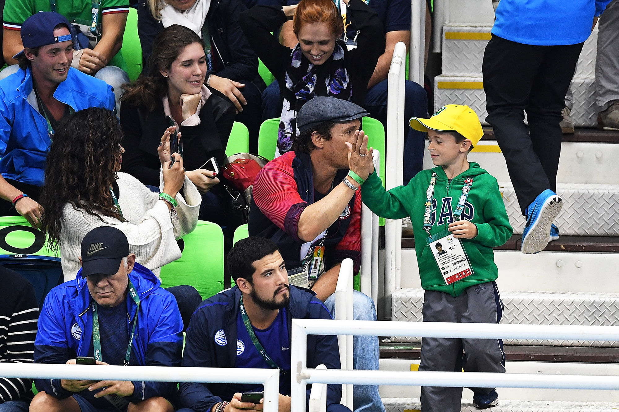 Matthew McConaughey gives a high five to a young boy during the swimming semifinals and finals on Day 5 of the Rio 2016 Olympic Games, on Aug. 9, 2016 in Rio de Janeiro, Brazil.