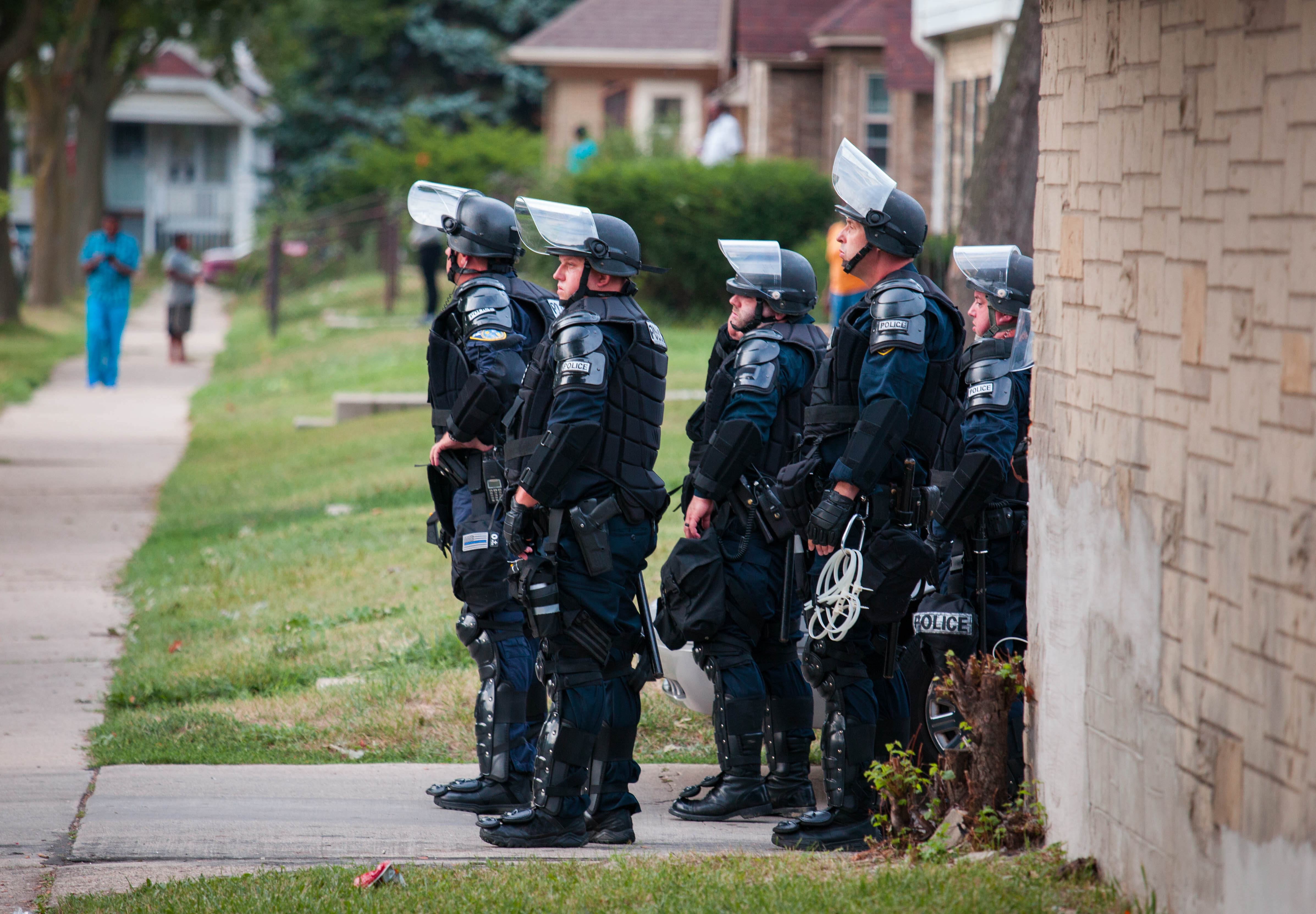 Police in riot gear wait in an alley after a second night of clashes between protestors and police in Milwaukee, Wisc., on Aug. 15, 2016.