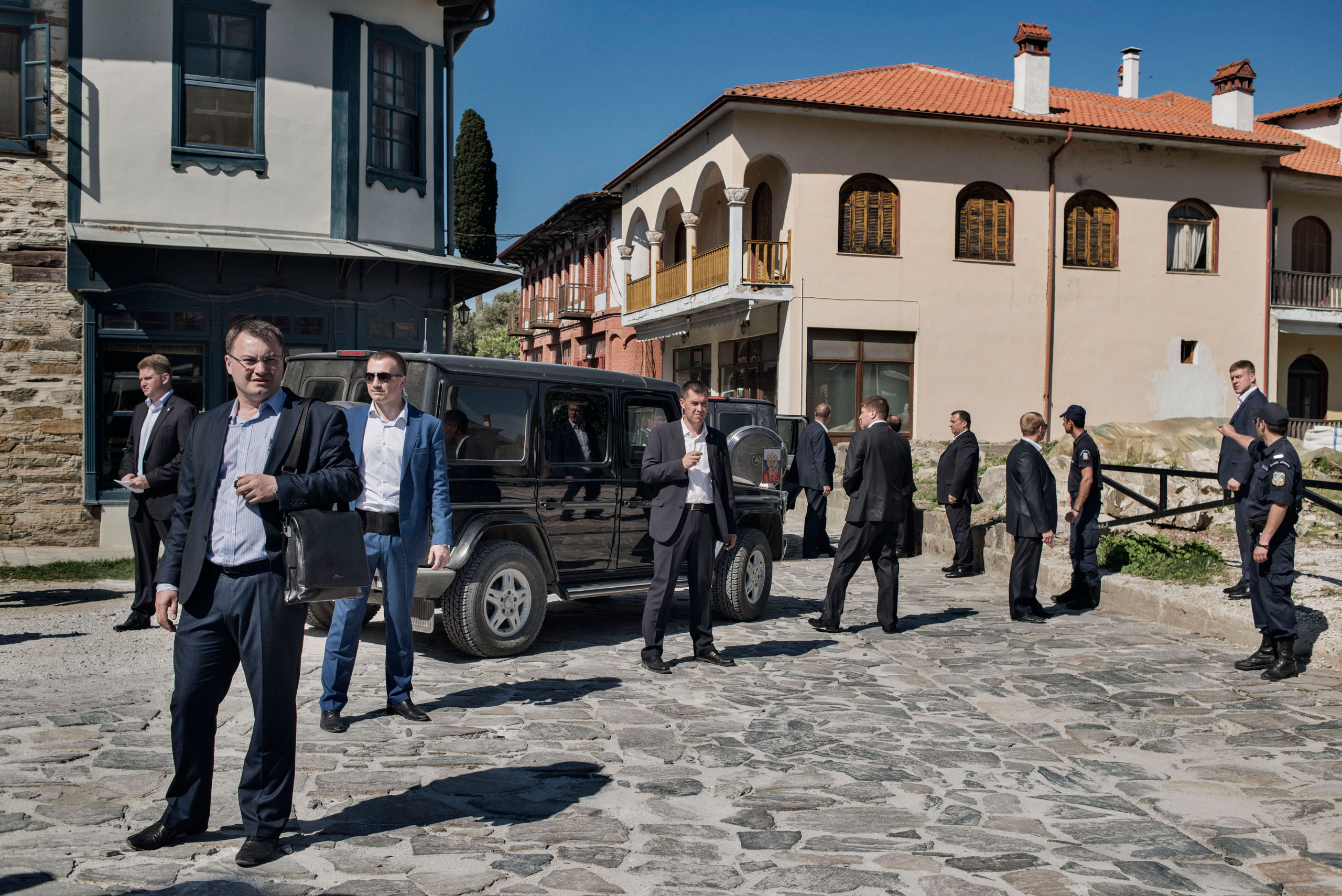 Russian secret service agents and Greek police officers surround a black Mercedes SUV carrying Russian President Vladimir Putin as he arrives in Karyes, the capital of Mount Athos, a self-governing community of Orthodox Christian monks in northern Greece, May 28, 2016.