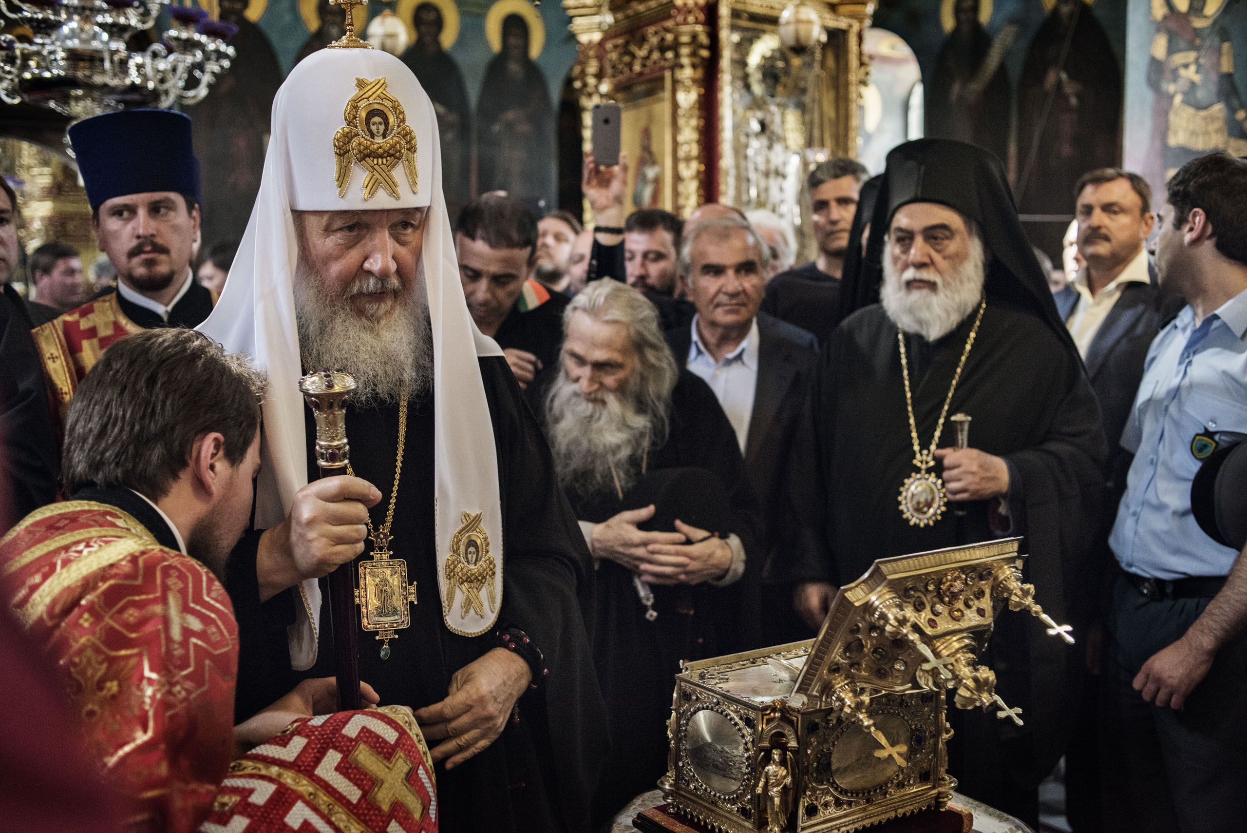 Patriarch Kirill of the Russian Orthodox Church stands before the reliquary, a bejeweled box containing a holy relic, at the main church in St. Panteleimon, the Russian monastery on Mount Athos, in northern Greece, May 27, 2016. Behind him bows the abbot of the monastery, Archimandrite Jeremiah (center), who is 100 years old.