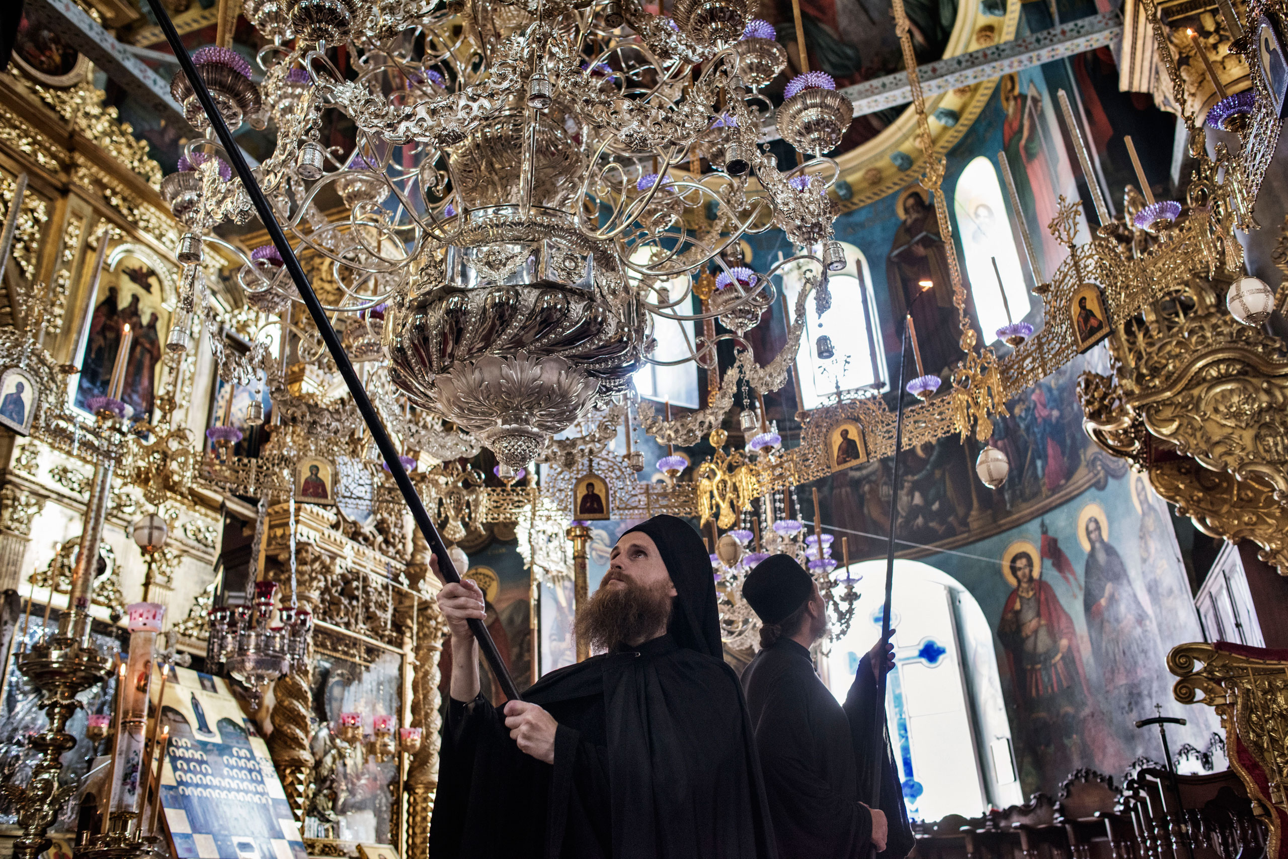Russian Orthodox monks light candles in preparation for the arrival of Patriarch Kirill, the head of the Russian Orthodox Church, inside the Monastery of St. Panteleimon, otherwise known as Rossikon ( The Russian ), May 27, 2016.