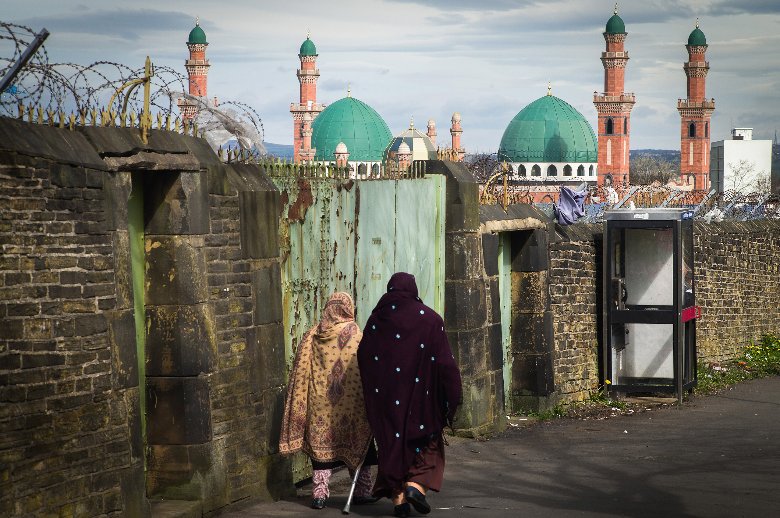 Muslim women walk in the foreground of the Suffa Tul Islam Central Mosque in the multicultural Bradford East constituency, where candidate Owais Rajput and his team canvassed ahead of May 7 elections in Bradford, England, on April 14, 2015.