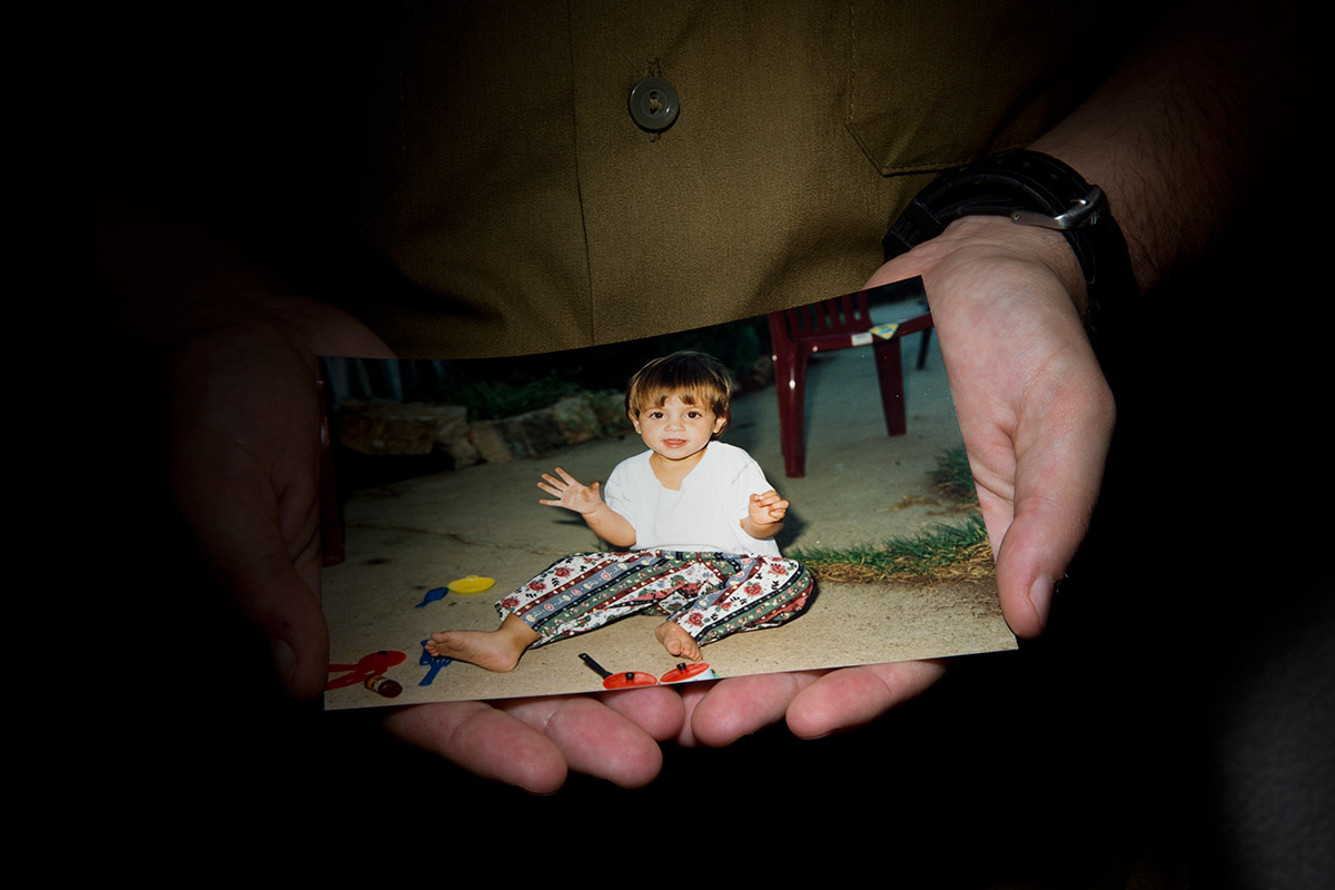 Lt. Shachar, a transgender IDF officer, holds a picture of himself as a young girl in Tel Aviv, Israel, in July.