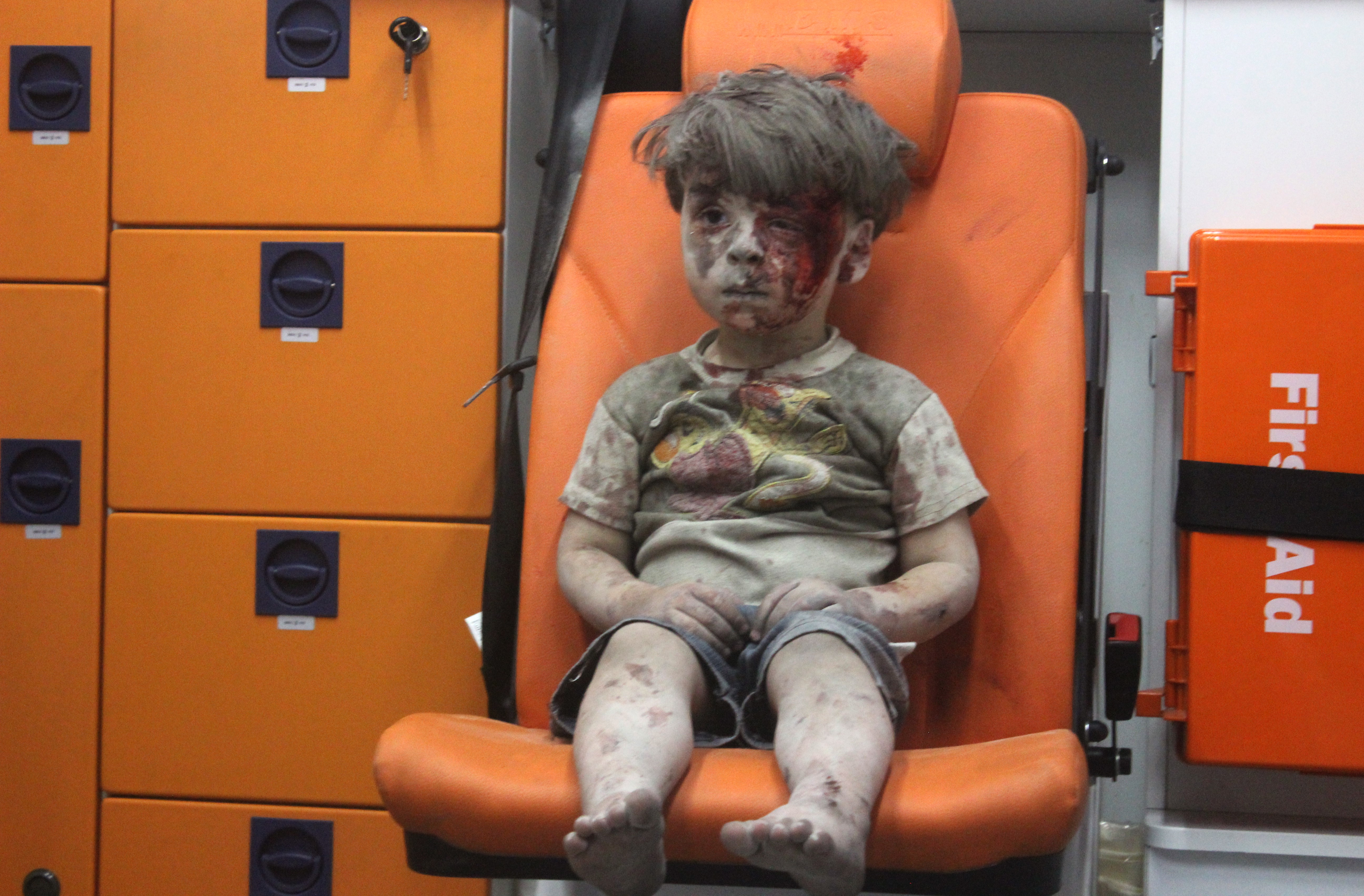 Five-year-old wounded Syrian boy Omran Daqneesh sits alone in the back of the ambulance after he sustained injuries during an airstrike targeting the Qaterji neighborhood of Aleppo on Aug. 17, 2016.