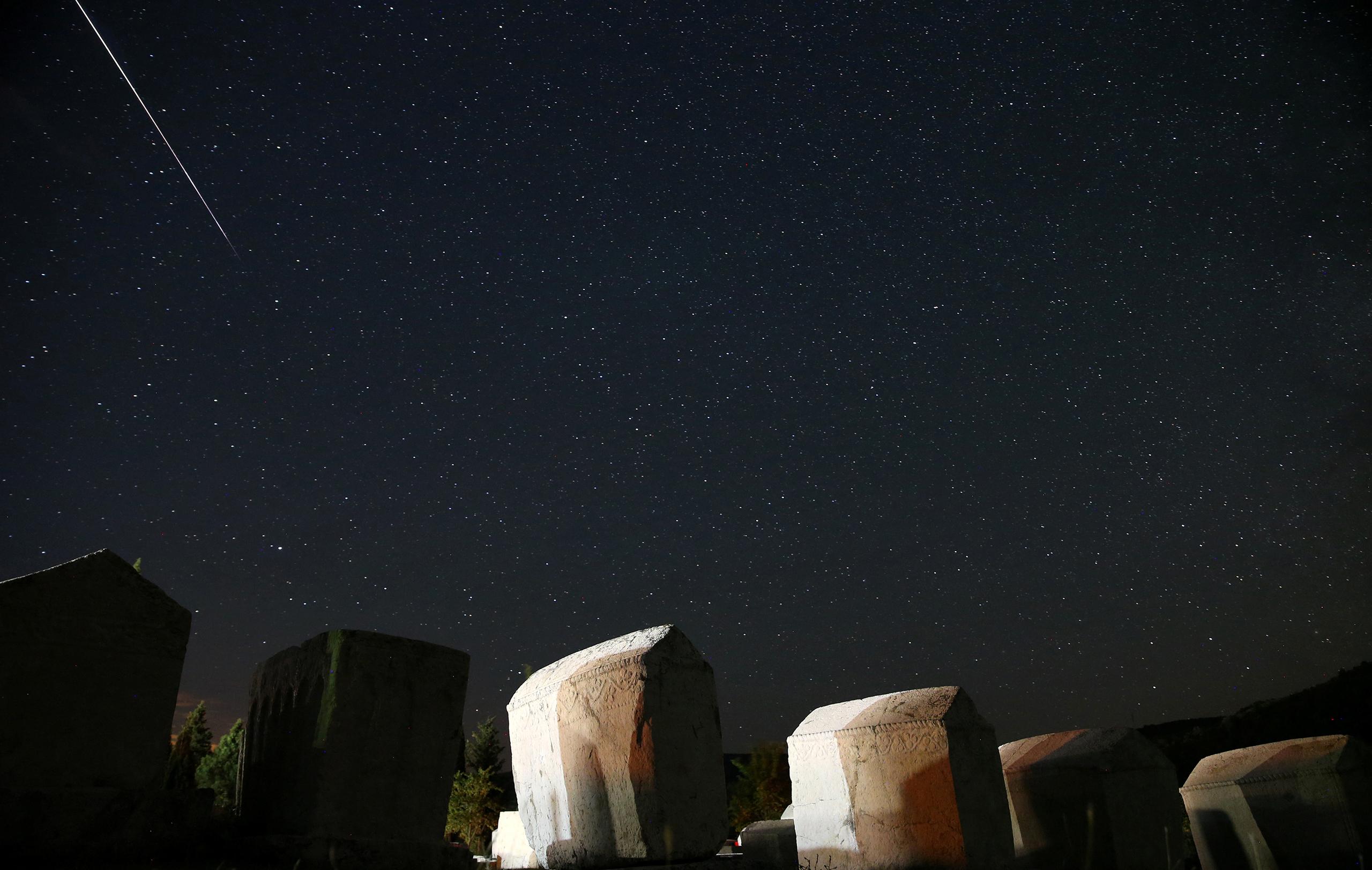 A meteor streaks past stars in the night sky above medieval tombstones in Radmilje near Stolac, south of Sarajevo, Bosnia and Herzegovina, Aug. 12, 2016.