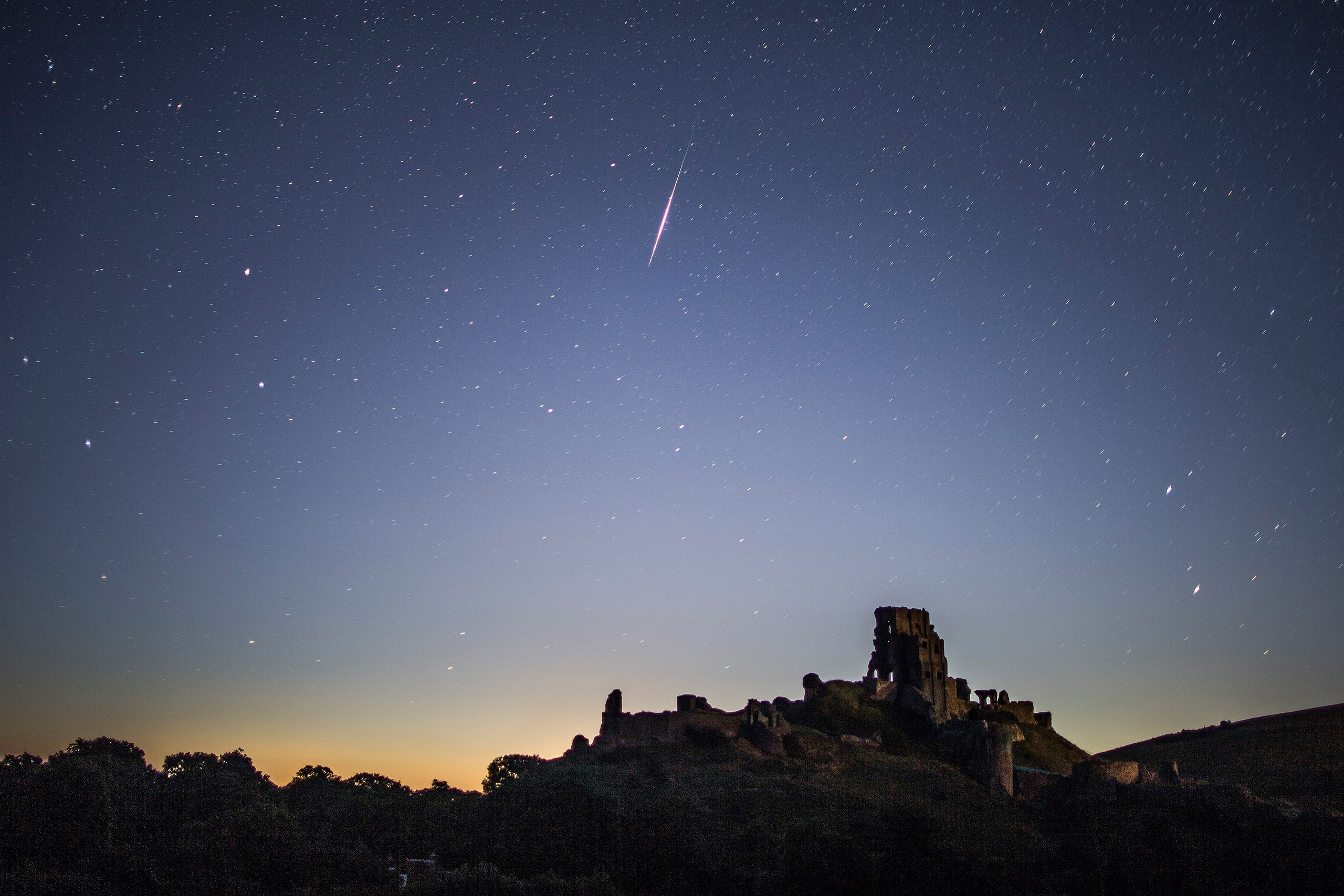 A Perseid meteor flashes across the night sky above Corfe Castle, United Kingdom, on Aug. 12, 2016.