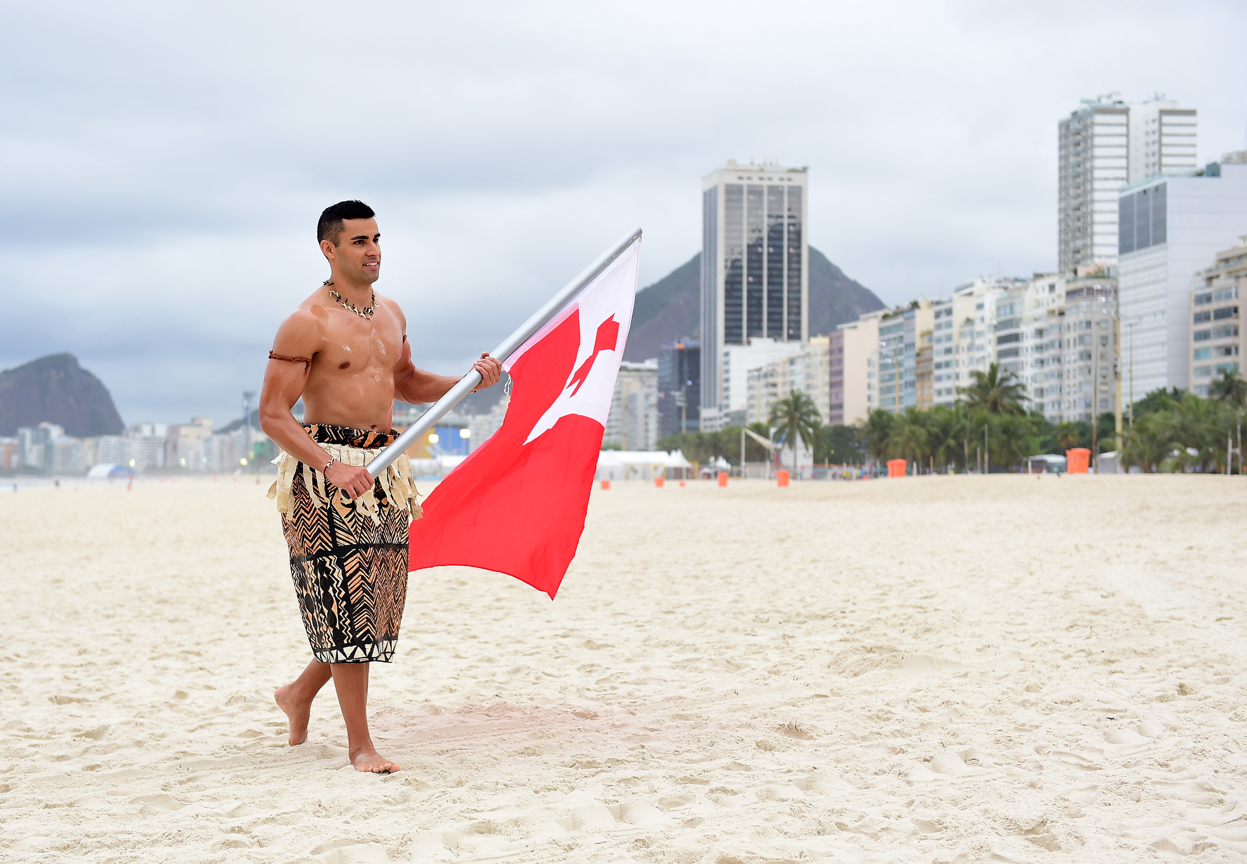 Pita Taufatofua of Tonga walks along the sand with his country's flag to the NBC Today show set at Copacabana Beach in Rio de Janeiro on Aug. 8, 2016.