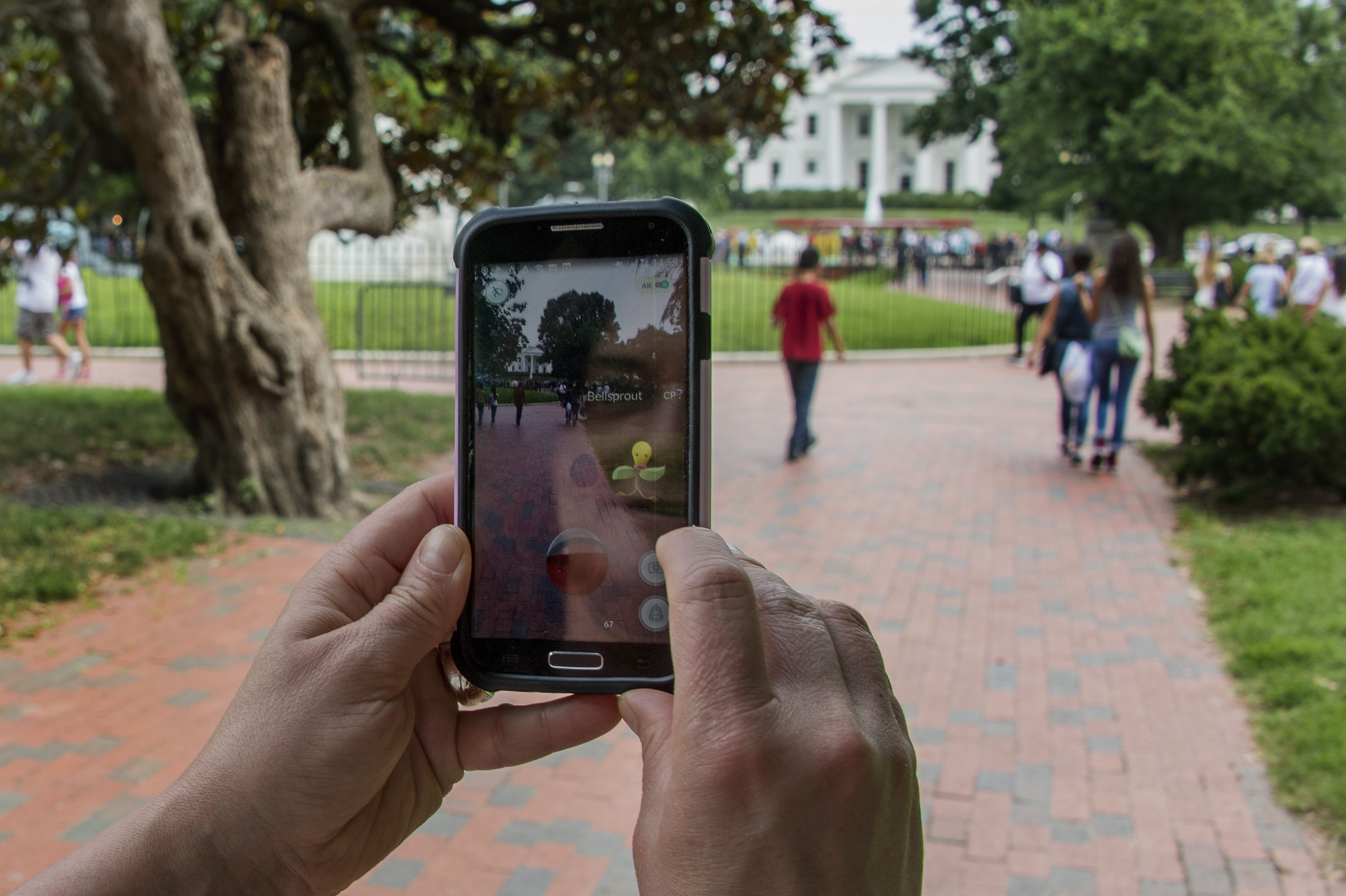 A woman plays Pokemon Go in Lafayette Park in front of the White House in Washington, DC,