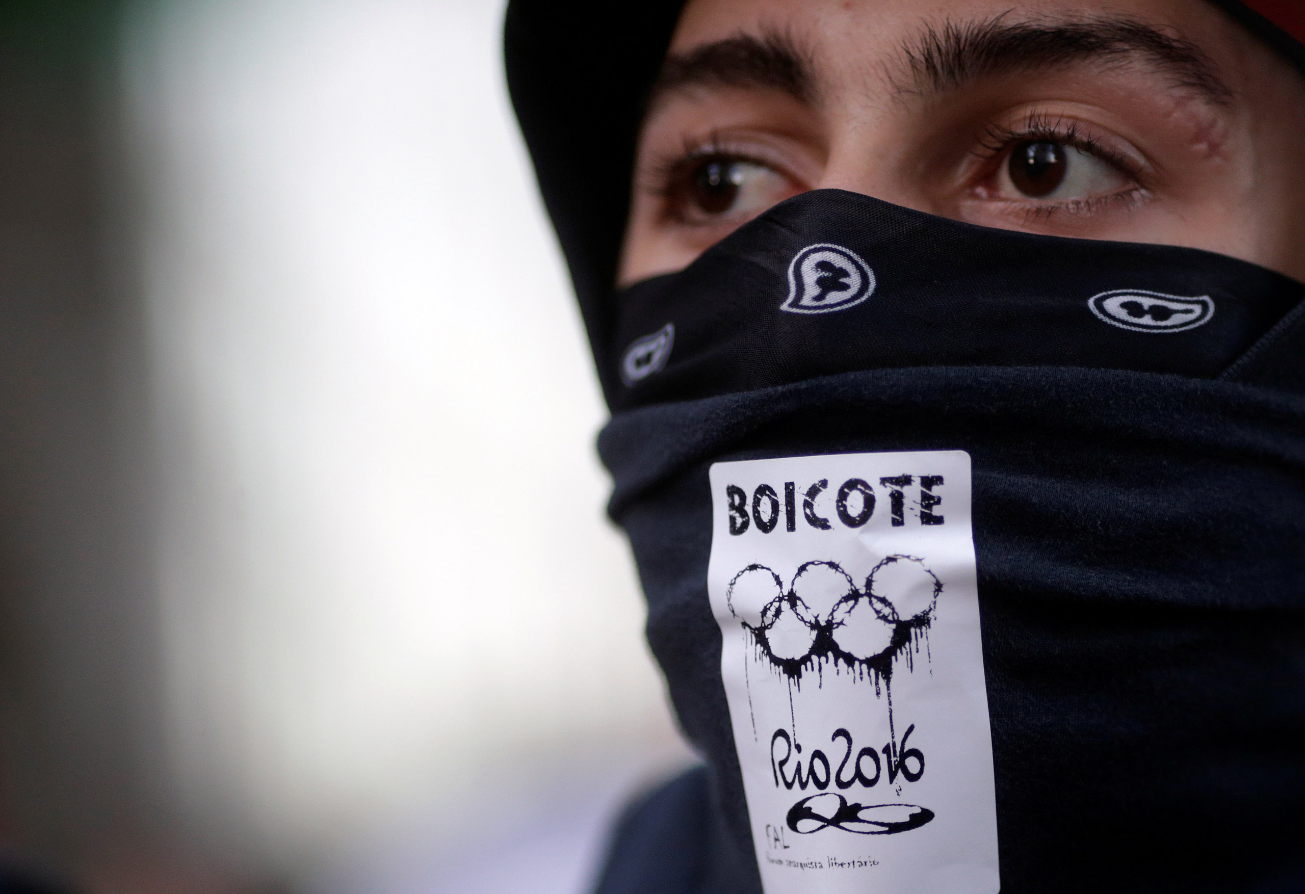 An anti-government demonstrator, with a sticker which reads  boycott  on his mask, attends a protest on the  Rio de Janeiro state economic crisis and against 2016 Rio Olympics, in Rio de Janeiro on July 6, 2016.