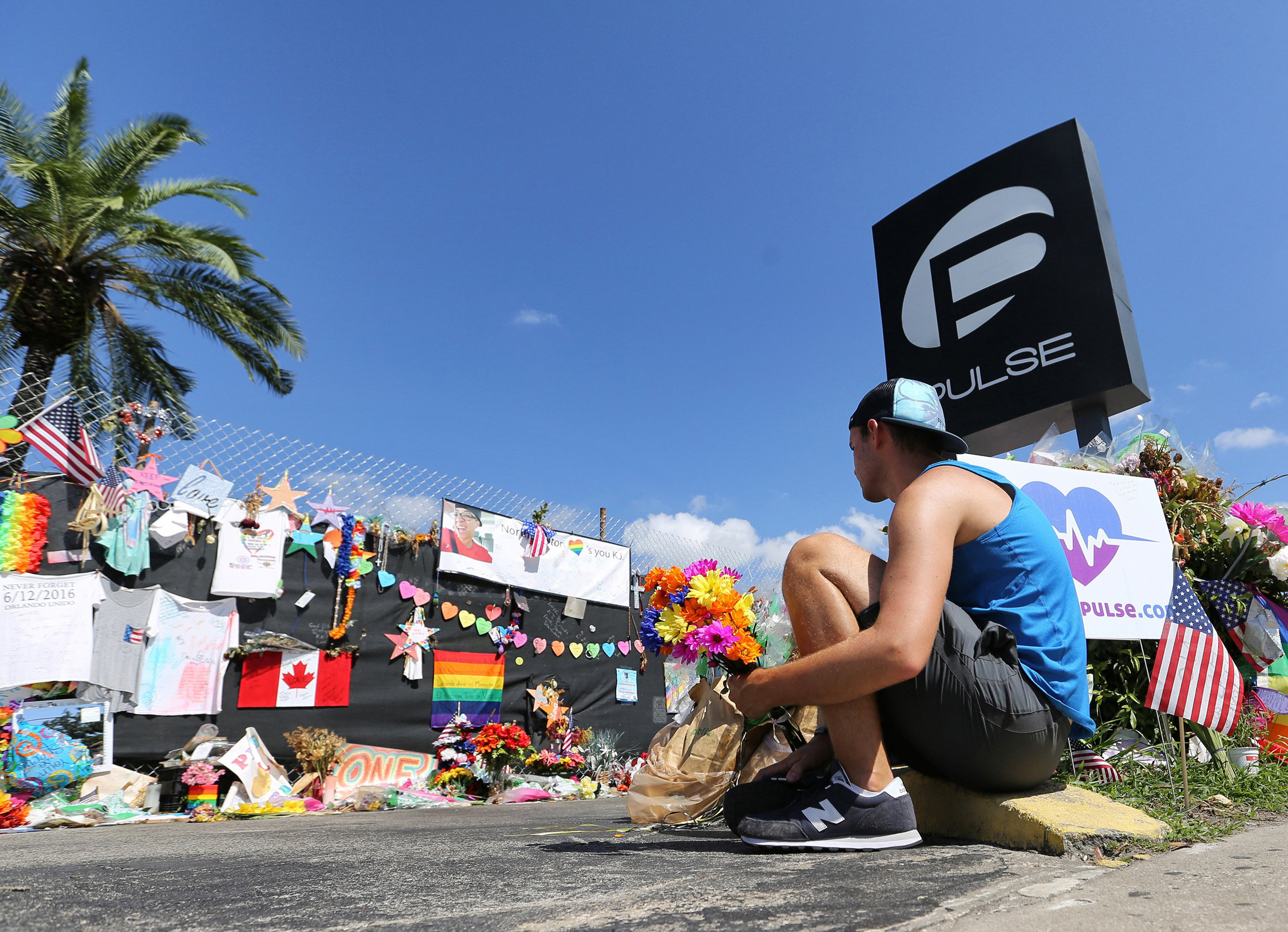 On the eve of the one-month anniversary of the Pulse nightclub massacre, a friend of two of the victims places flowers as visitors continue to flock to the club to their pay their respects in Orlando on July 11, 2016.