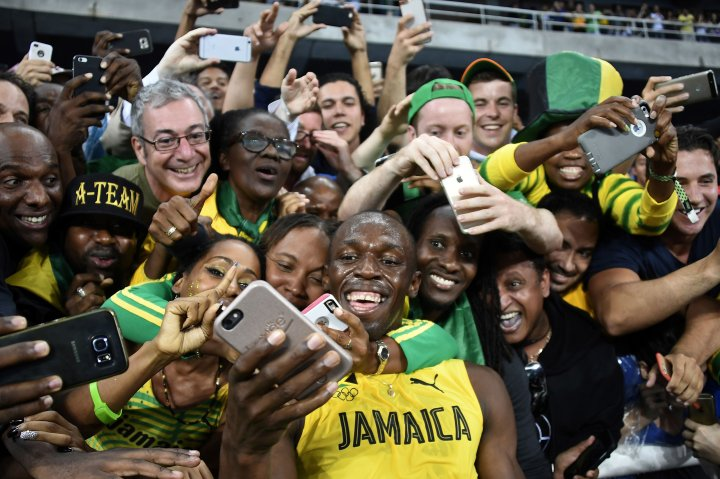 Jamaica's Usain Bolt takes selfie photos as he celebrates with fans after winning the Men's 200m Final during the athletics event at the Rio 2016 Olympic Games at the Olympic Stadium in Rio de Janeiro on Aug. 18, 2016.