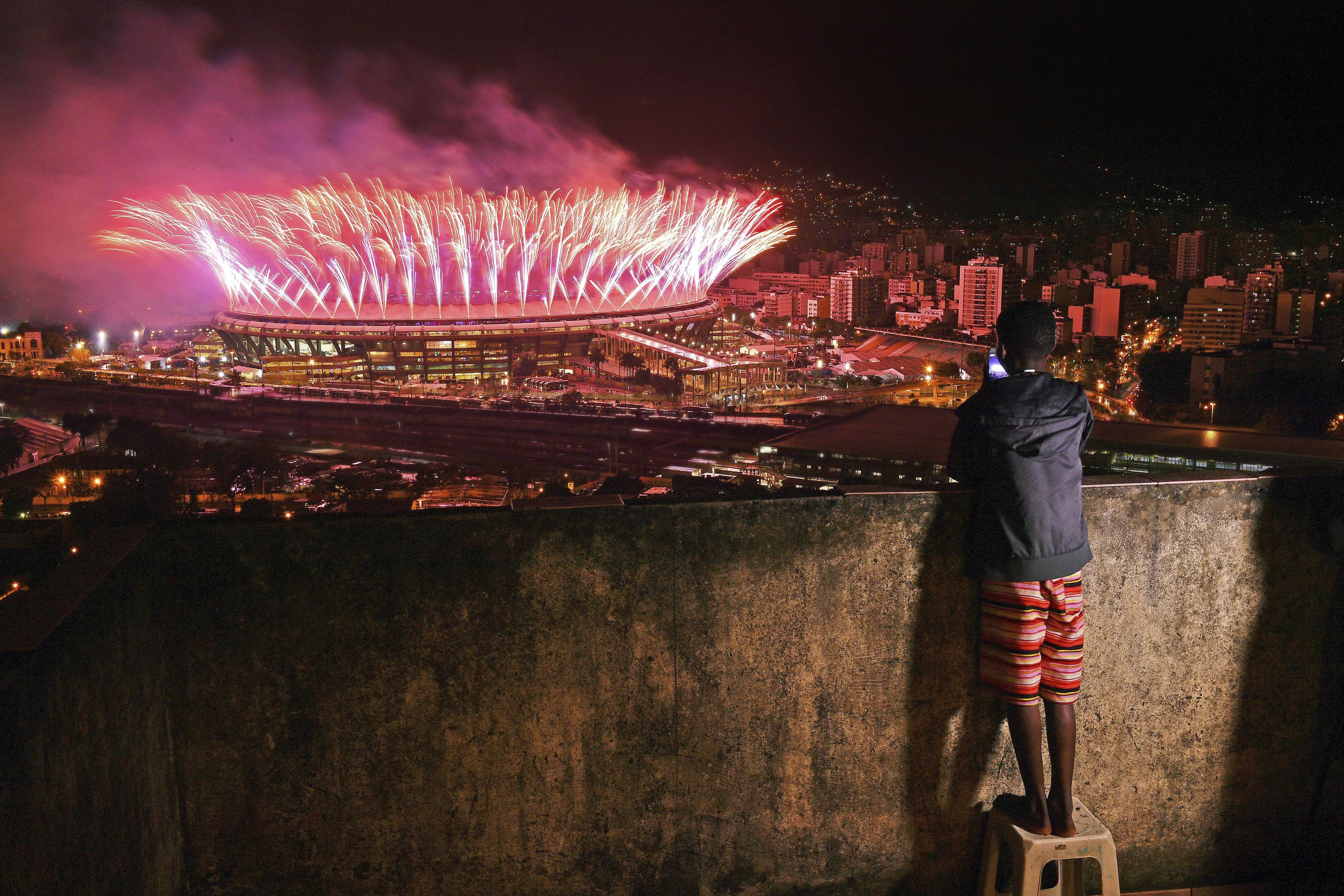 A boy watches the closing ceremony of the Rio Olympics from the Mangueira favela on Aug. 21