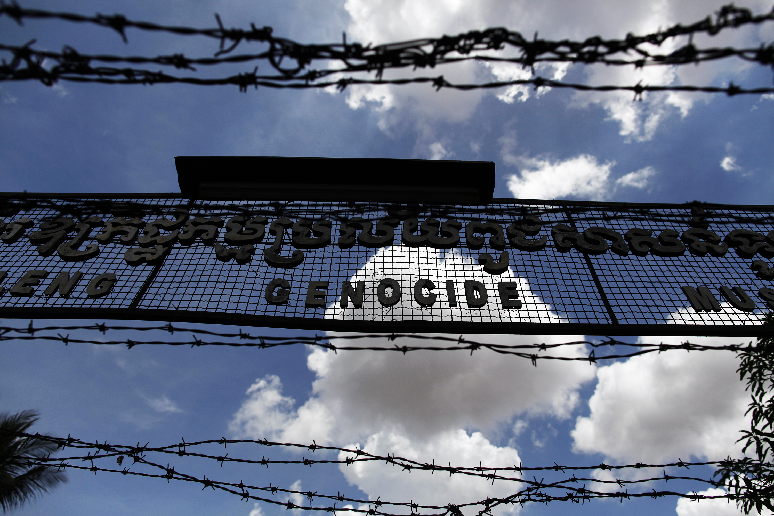 The sign above the entrance of Tuol Sleng Genocide Museum, also known as the notorious security prison S-21, is seen through razor wire in Phnom Penh July 4, 2010.