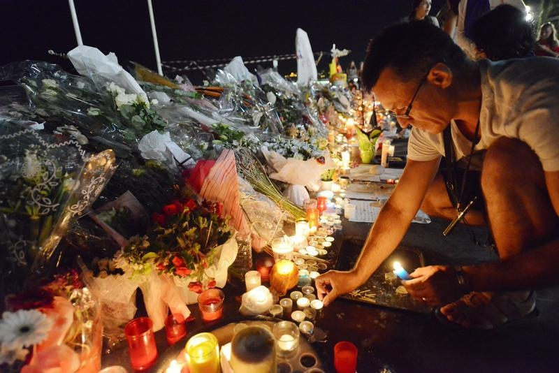A man places candles near flowers that were left in tribute at makeshift memorials to the victims of the truck attack along the Promenade des Anglais in Nice, France, July 18, 2016