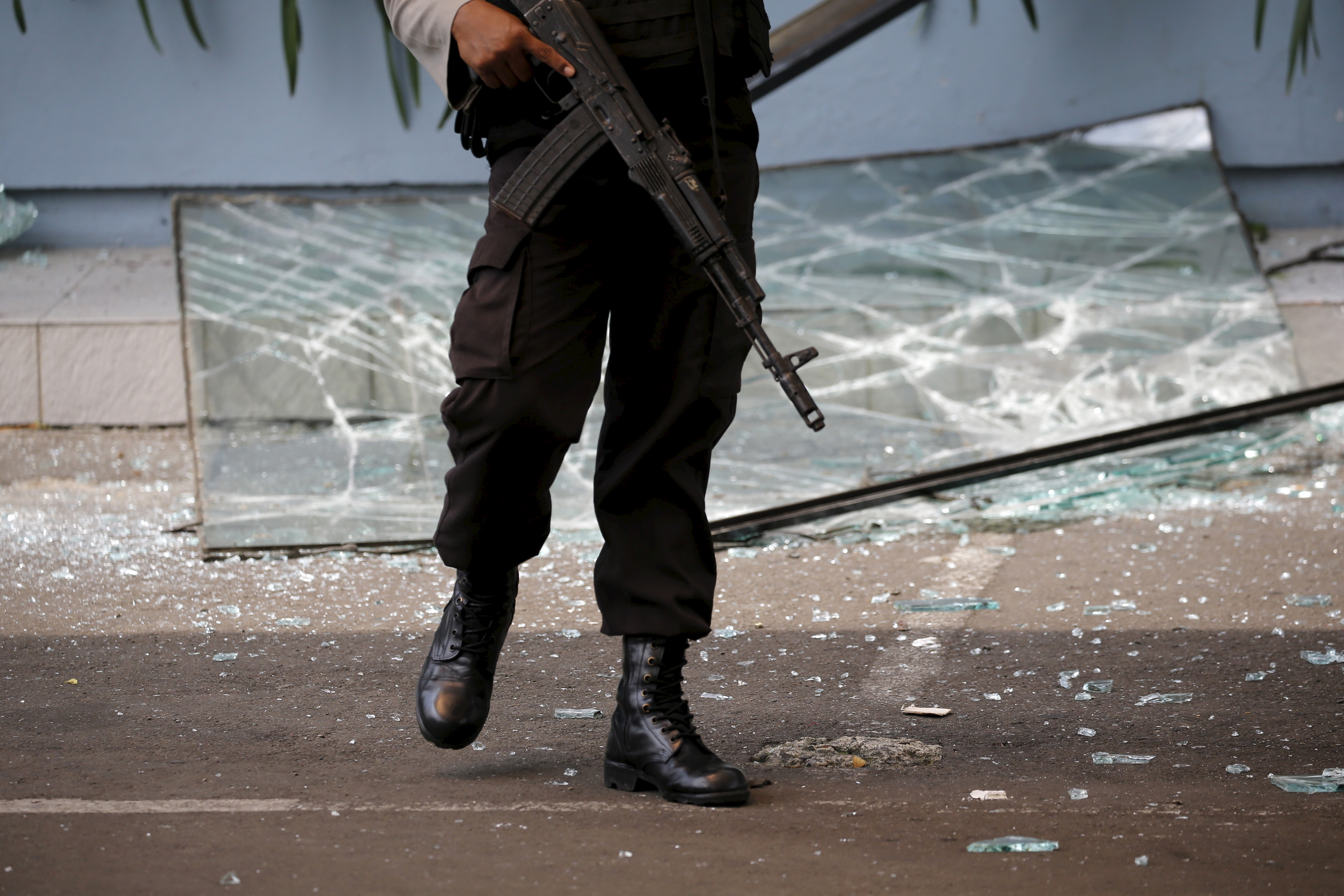 An Indonesian policeman holds a weapon while walking near a broken glass window from a Starbucks outlet in Jakarta on Jan. 14, 2016, after militants launched a deadly gun-and-bomb assault