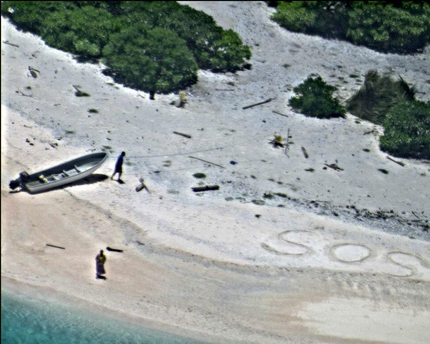 A pair of stranded mariners signaling for help by writing 'SOS' in the sand as a US Navy P-8A Poseidon aircraft crew from Patrol Squadron (VP) 8 flies over in support of a Coast Guard search and rescue mission at East Fayu Island, Micronesia, on 25 August 2016.
