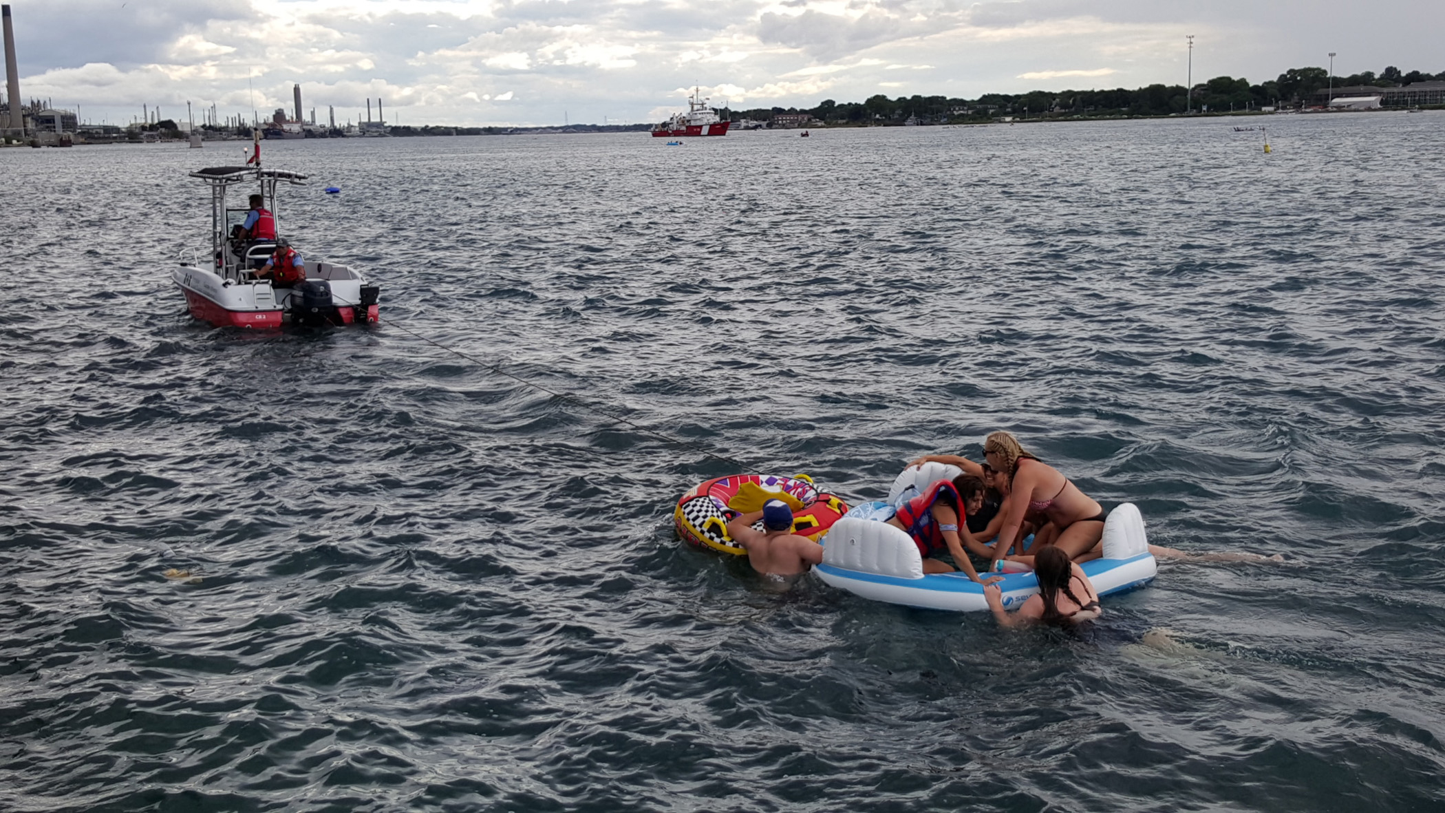 A Canadian Coast Guard ship tows floatation devices used by U.S. partiers to the Canadian side of the St. Clair River between Michigan and Ontario on Aug. 21, 2016.