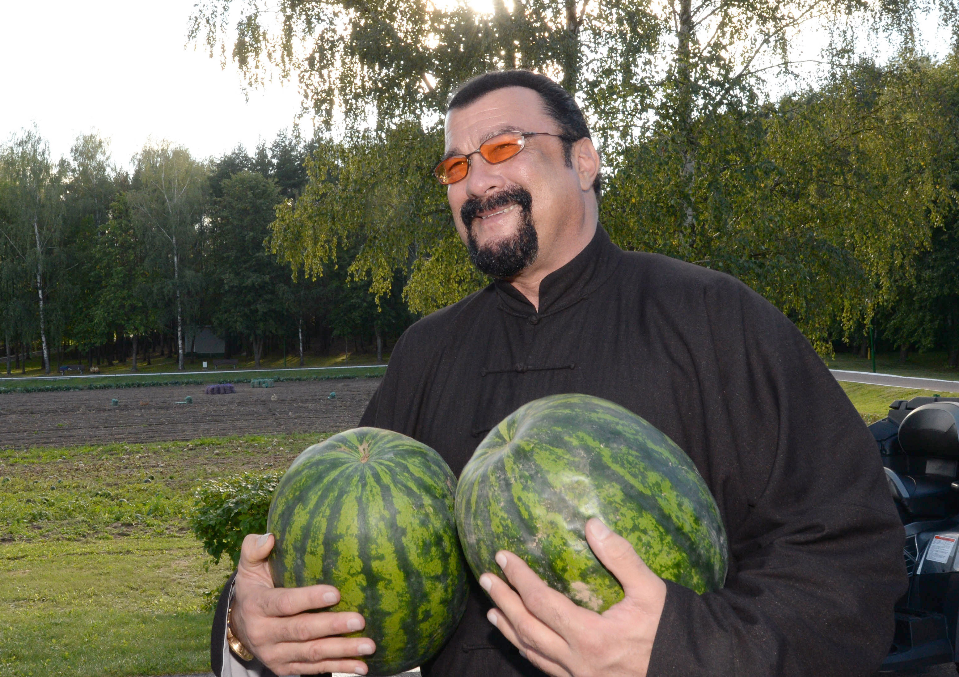 U.S. actor Steven Seagal holds two water melons during his meeting with the Belarus President at his residence on August 24, 2016.