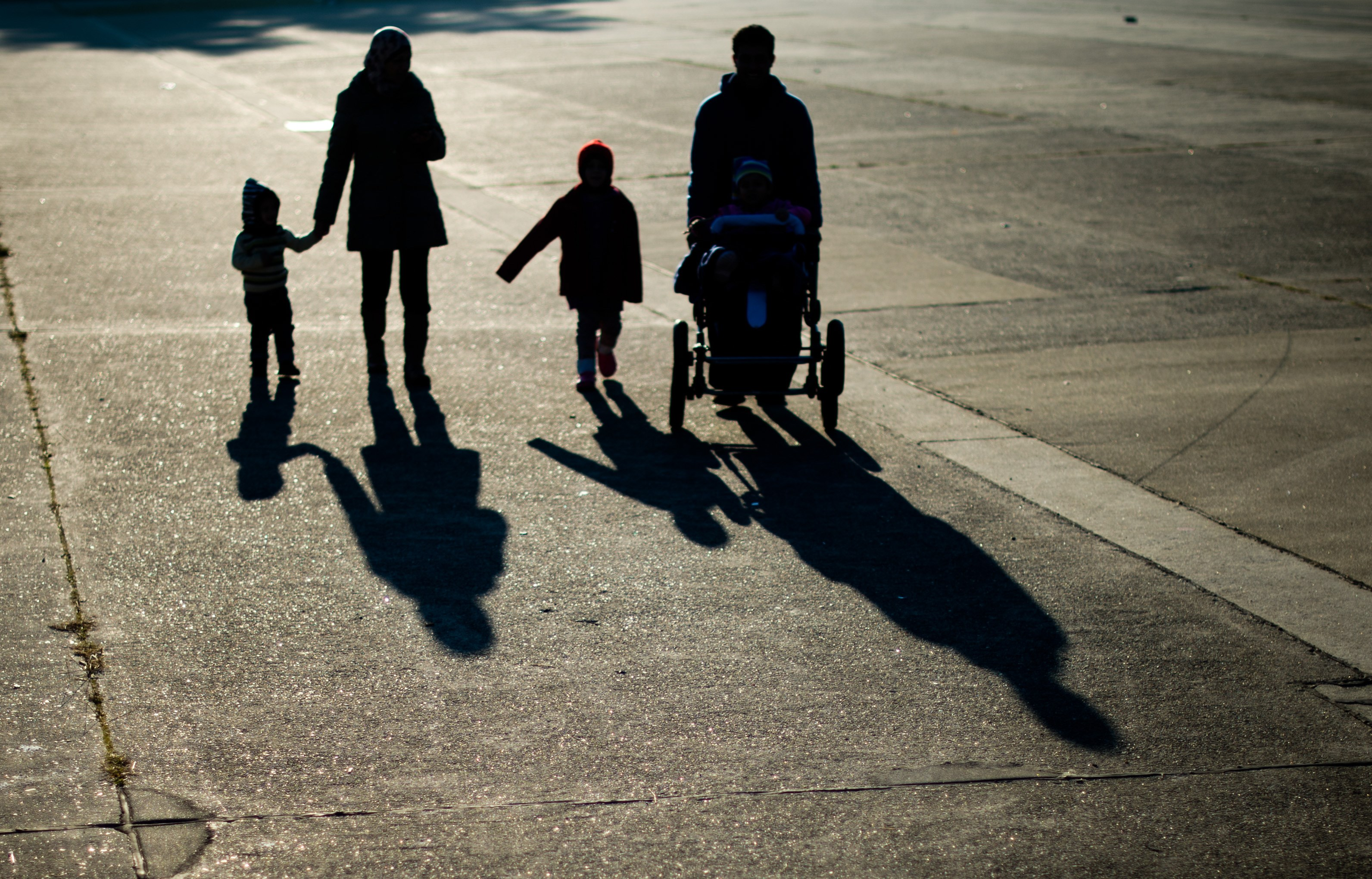 A refugee family from Syria cast long shadows as they walk  in Ehra-Lessien, in central Germany, on Nov. 3, 2015