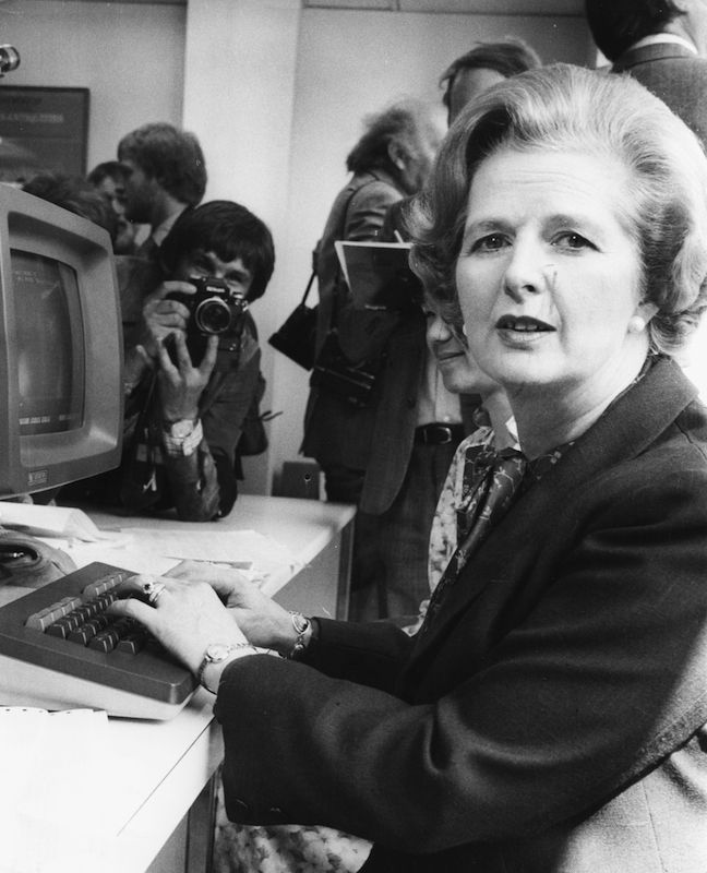 British Prime Minister Margaret Thatcher is photographed by the press as she tries out a  computer during a visit to Logica Ltd in London, 1980.