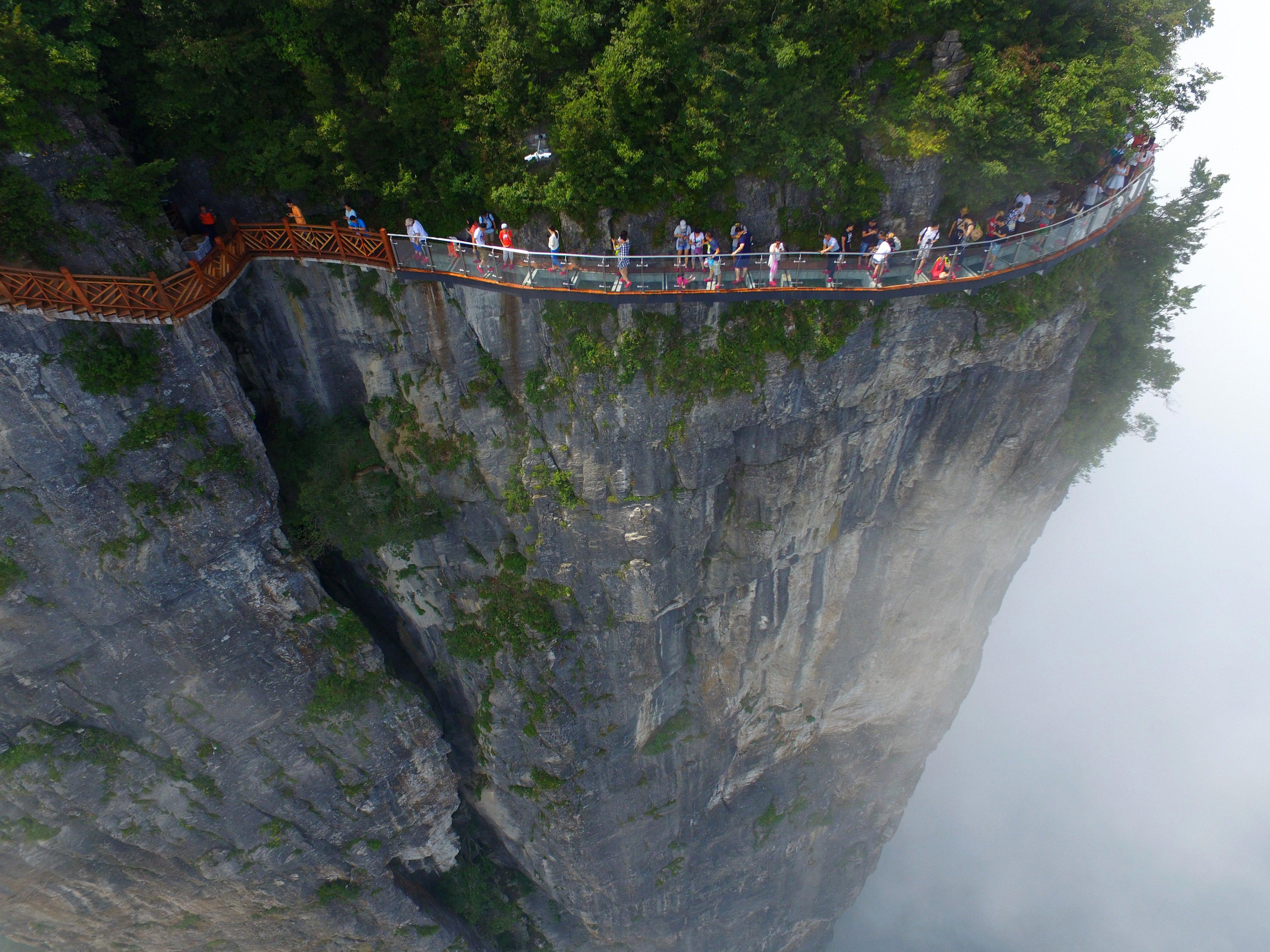 Tourists walking on the glass skywalk clung the cliff of Tianmen Mountain, on Aug. 1, 2016 in Zhangjiajie, China.