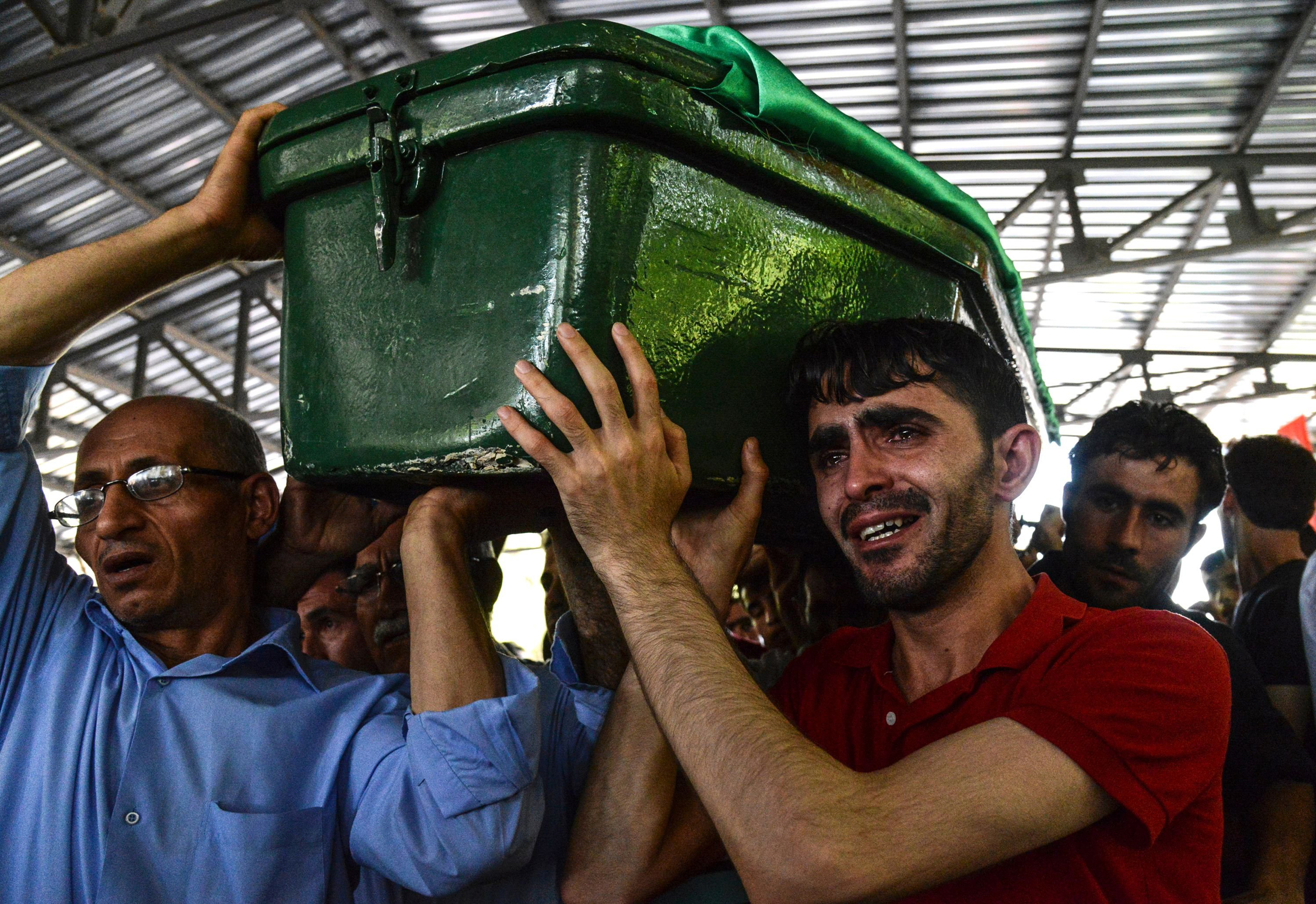 A man cries as he carries a coffin during a funeral for victims of last night's attack on a wedding party that left 50 dead in Gaziantep in southeastern Turkey near the Syrian border on Aug. 21, 2016.