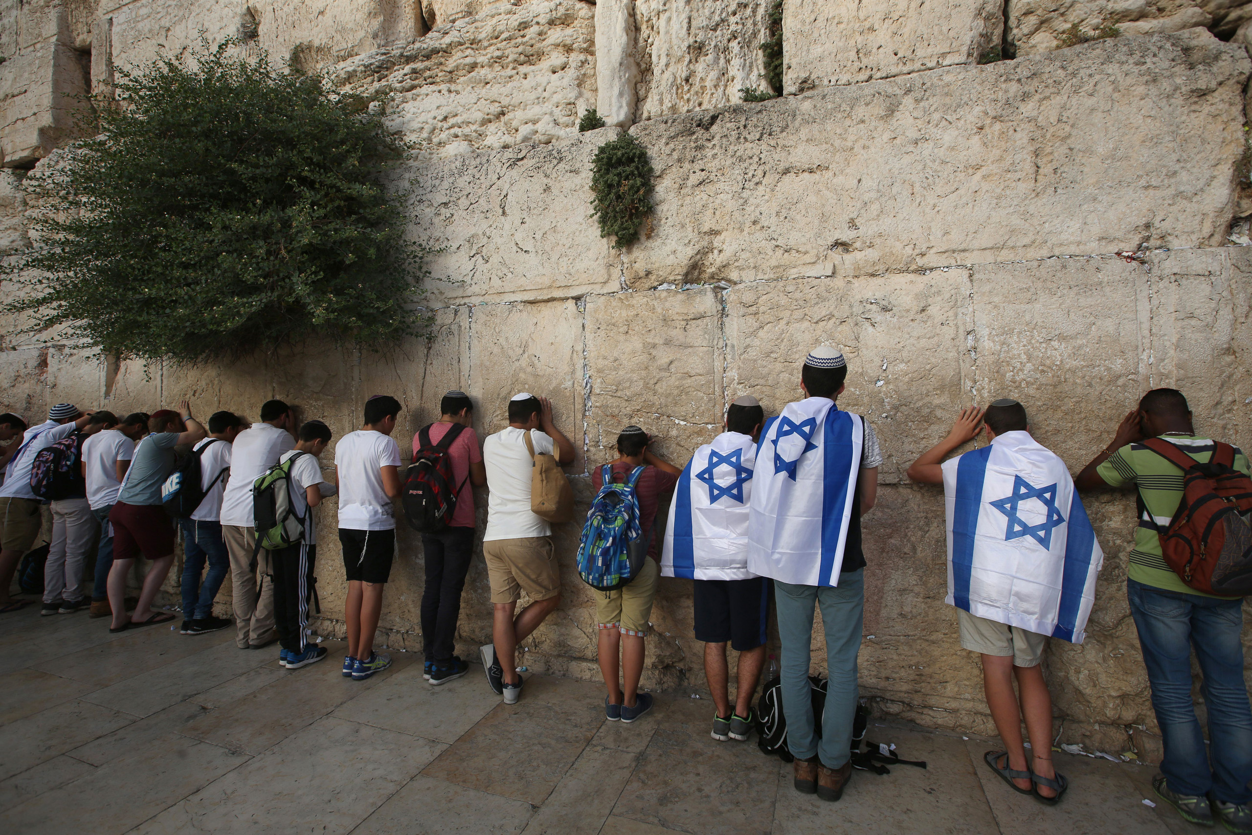 Israeli men pray at the Western Wall in Jerusalem's old city, as they celebrate Jerusalem Day, that marks the anniversary of the  reunification  of the holy city after Israel captured the Arab eastern sector from Jordan during the 1967 Six-Day War on June 5, 2016.