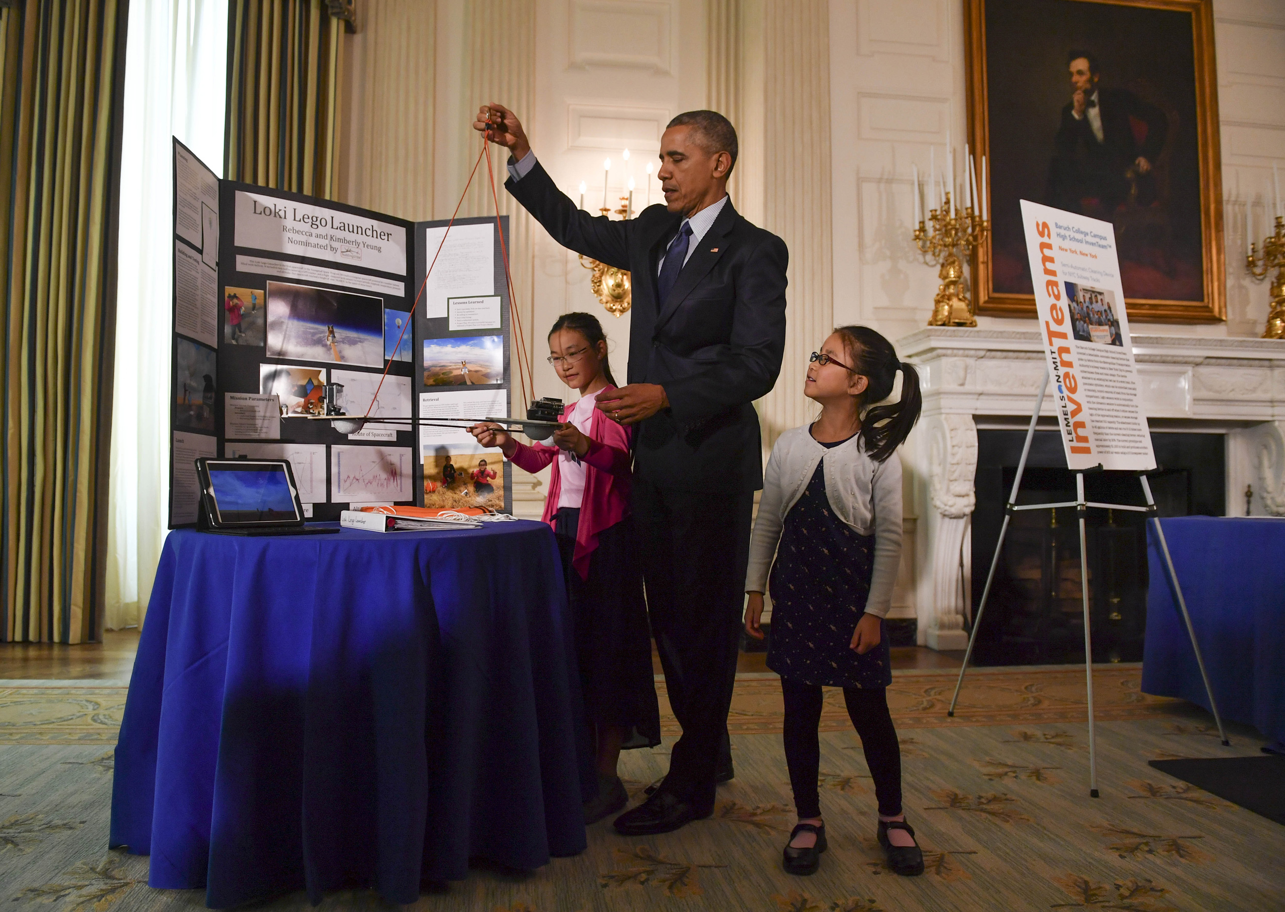 Sisters Kimberly, 9, right, and Rebecca Yeung, 11, of Seattle, WA., look on as President Barack Obama lifts their spacecraft science fair project during the sixth and final, annual White House Science Fair at The White House in Washington on April 13, 2016.
