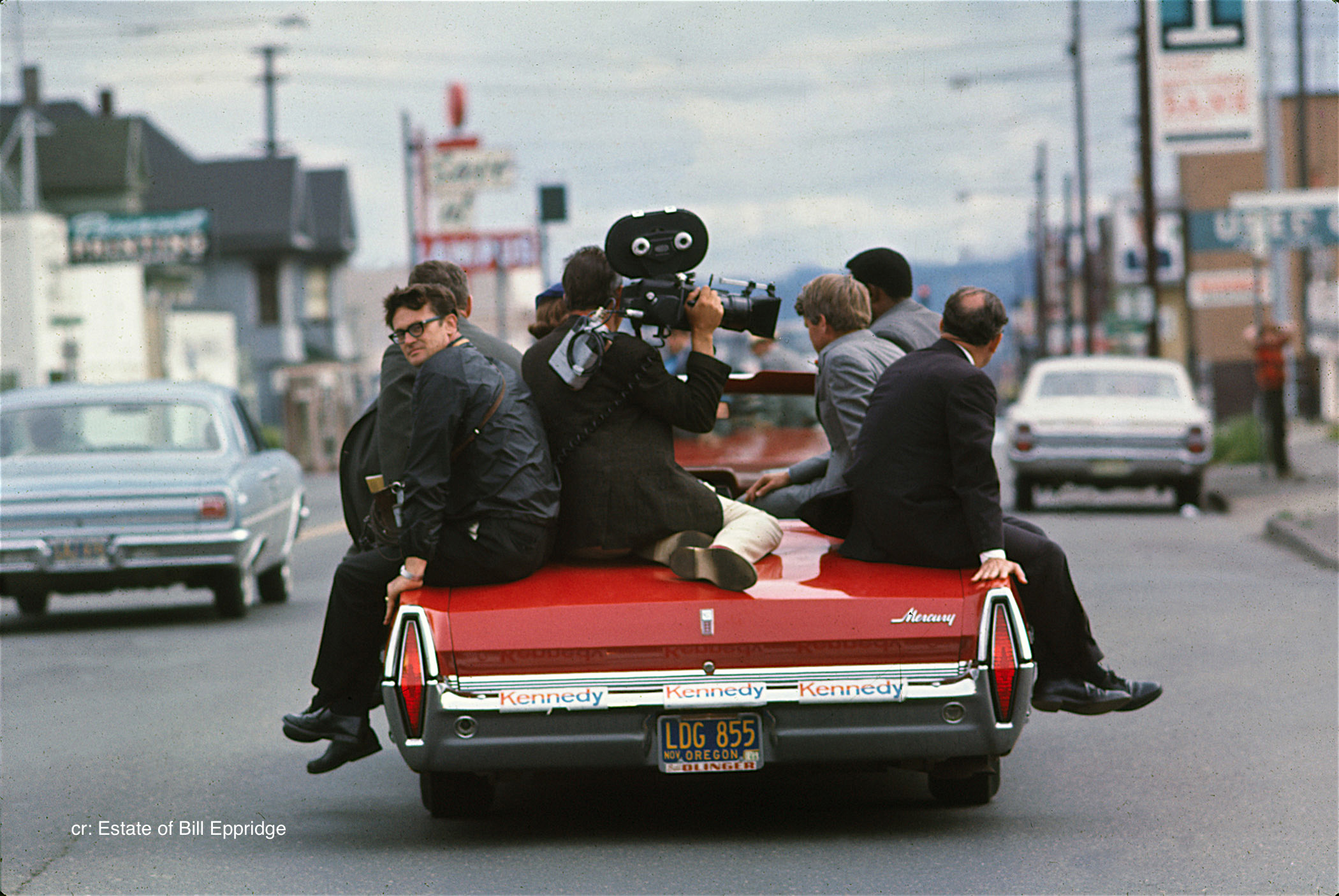 Senator Robert F. Kennedy riding with the press on the back of a convertible, Oregon, April or                               May 1968.