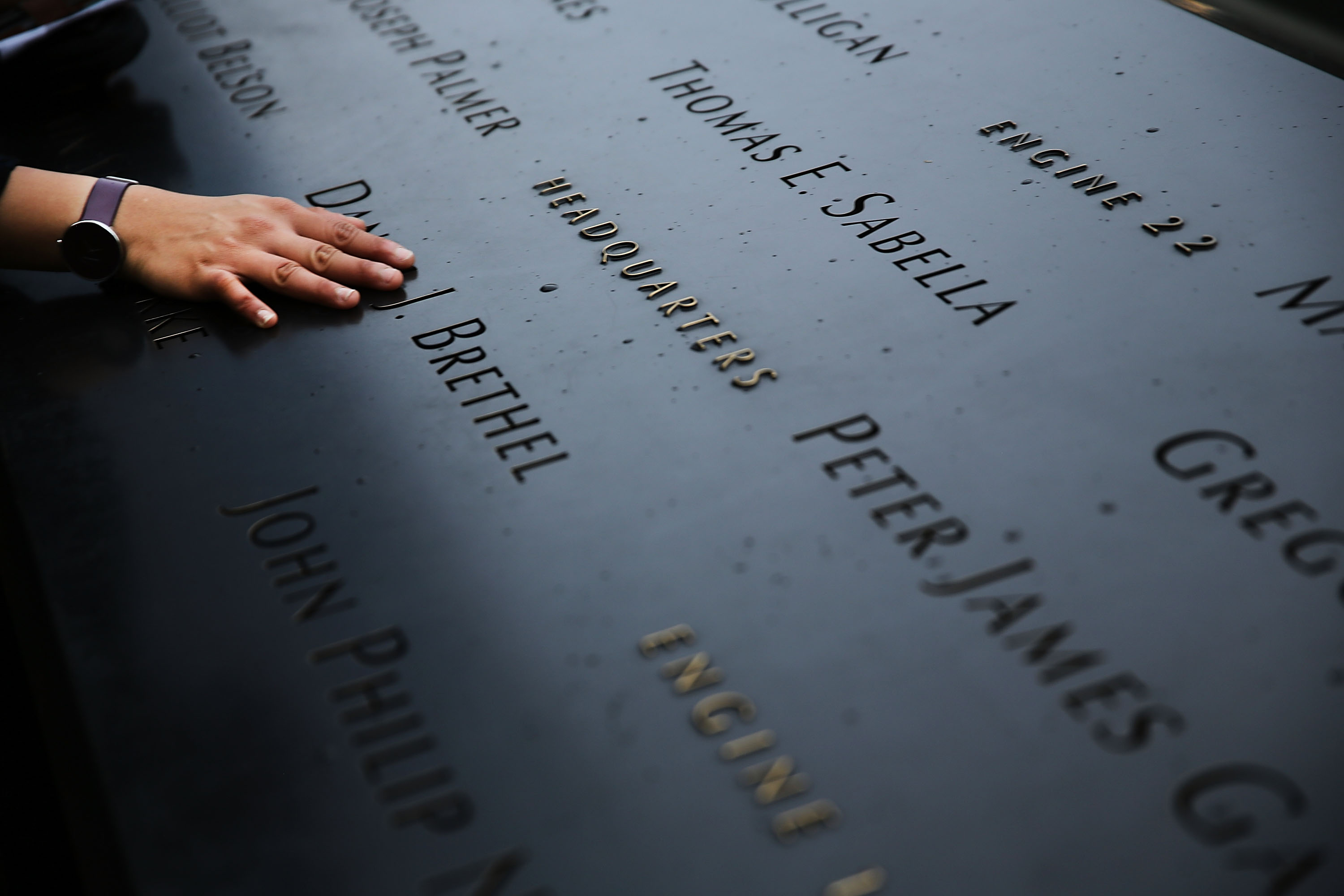 A woman places a hand on the names engraved along the South reflecting pool at the Ground Zero memorial site in New York City, on May 15, 2014.