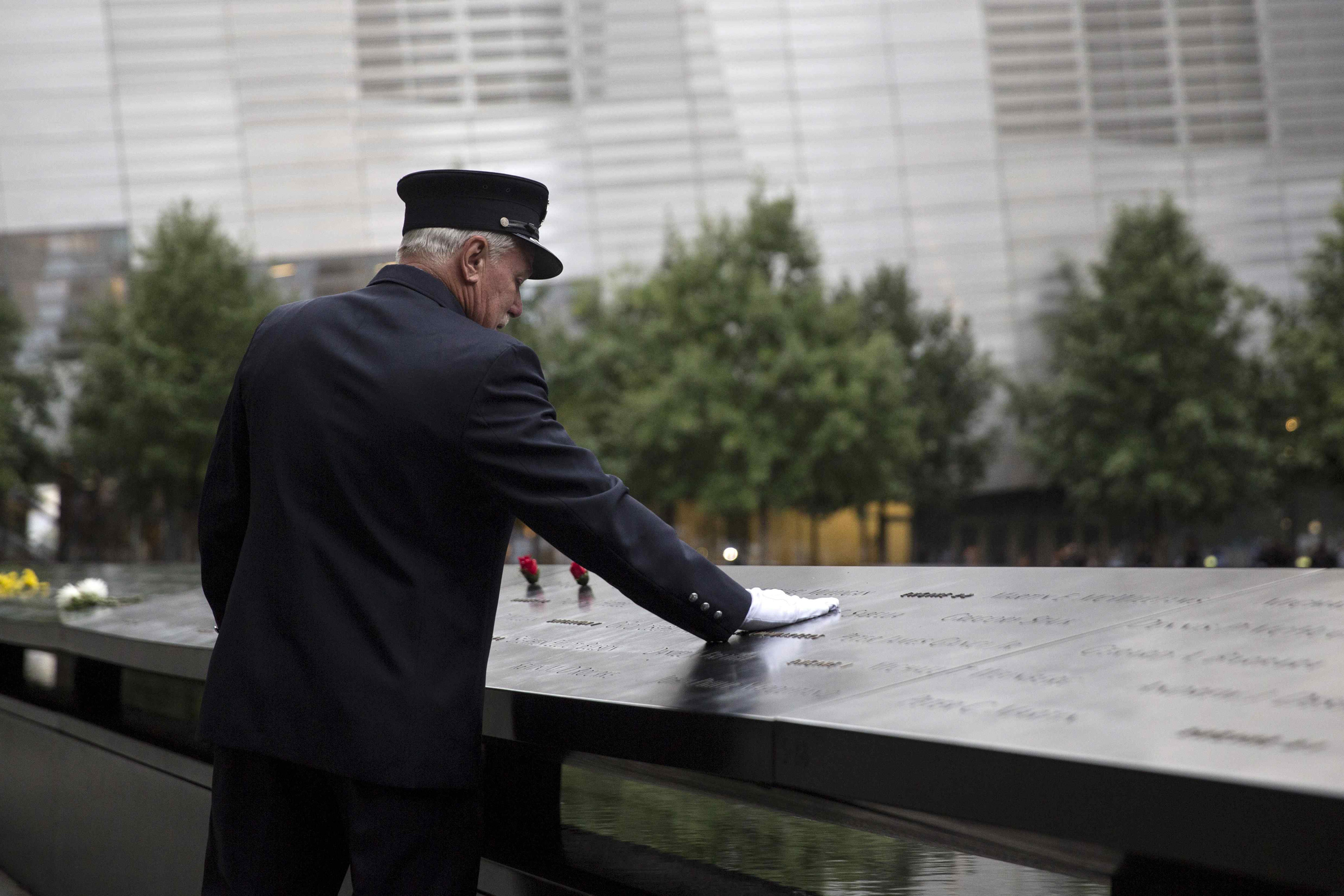 A member of the New York Fire Department places his hand on the memorial before a ceremony marking the 14th anniversary of the 9/11 attacks, at the National September 11 Memorial and Museum in Lower Manhattan in New York September 11, 2015.
