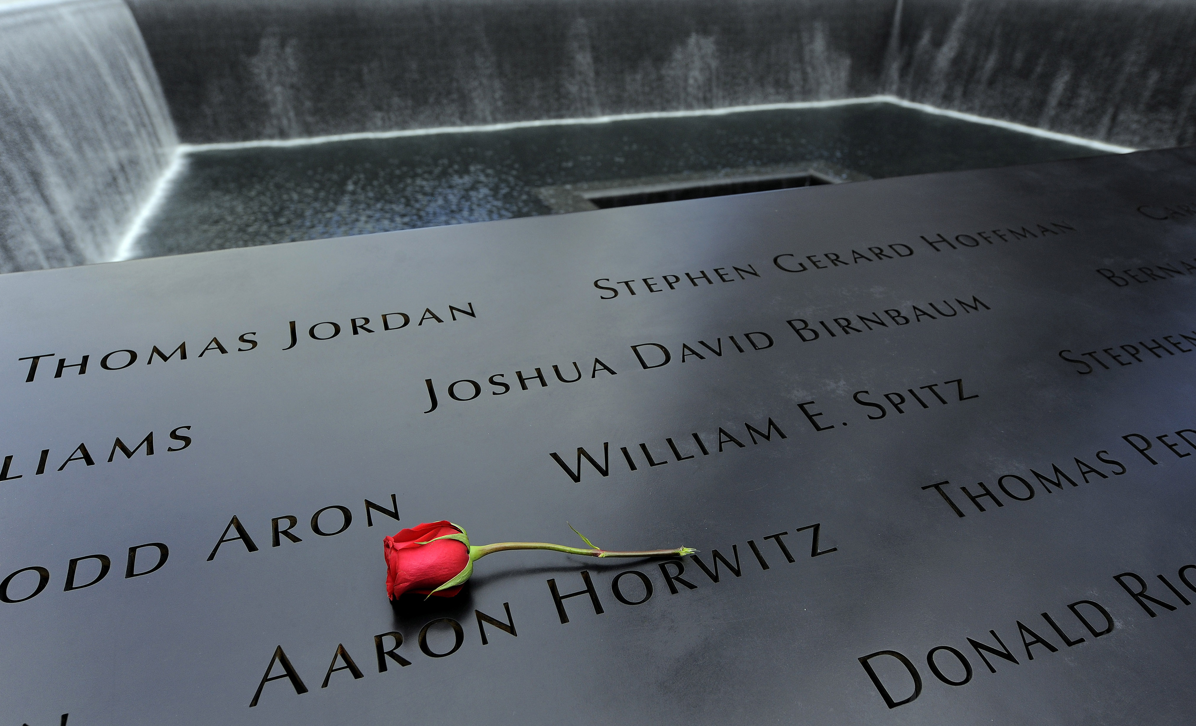 A rose is placed on the names inscribed around the North Pool of the 9/11 Memorial during tenth anniversary ceremonies at the site of the World Trade Center in New York on Sept. 11, 2011.
