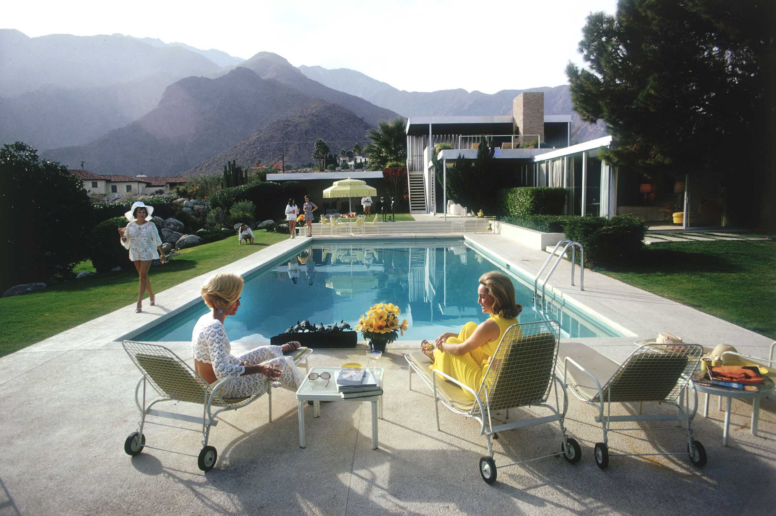 Slim Aarons, Stayley Wise Gallery, N.Y.: Oct. 14 - Nov. 26                               (Caption: Poolside Gossip, 1970: Lita Baron, Nelda Linsk, and Helen Dzo Dzo at a desert house in Palm Springs designed by Richard Neutra for Edgar Kaufman)