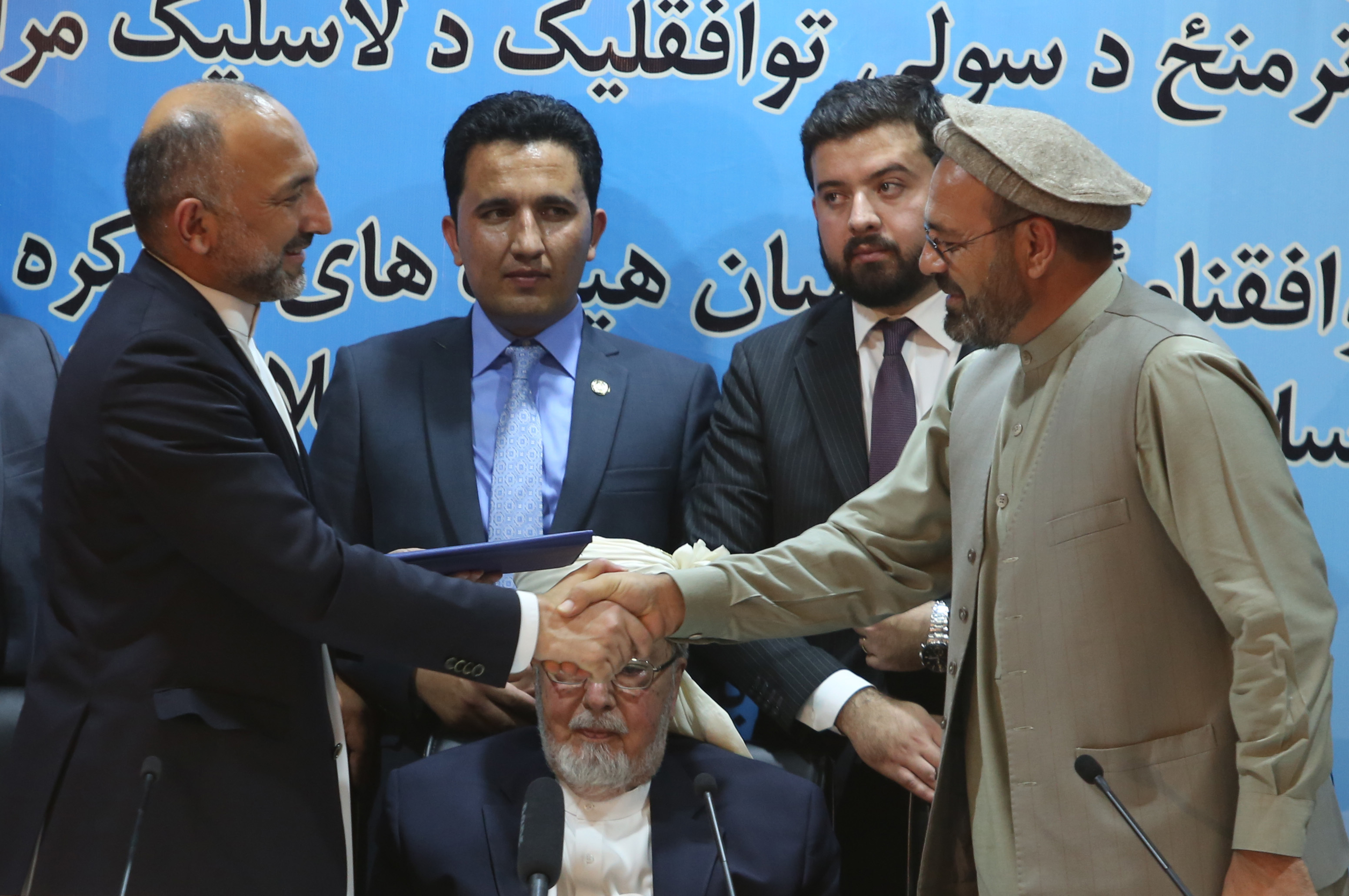 Afghanistan national security adviser Mohammad Hanif Atmar, left, and Amin Karim, representative of Gulbuddin Hekmatyar, right, shake hands after signing a peace deal in Kabul, Afghanistan, Thursday, Sept. 22, 2016.