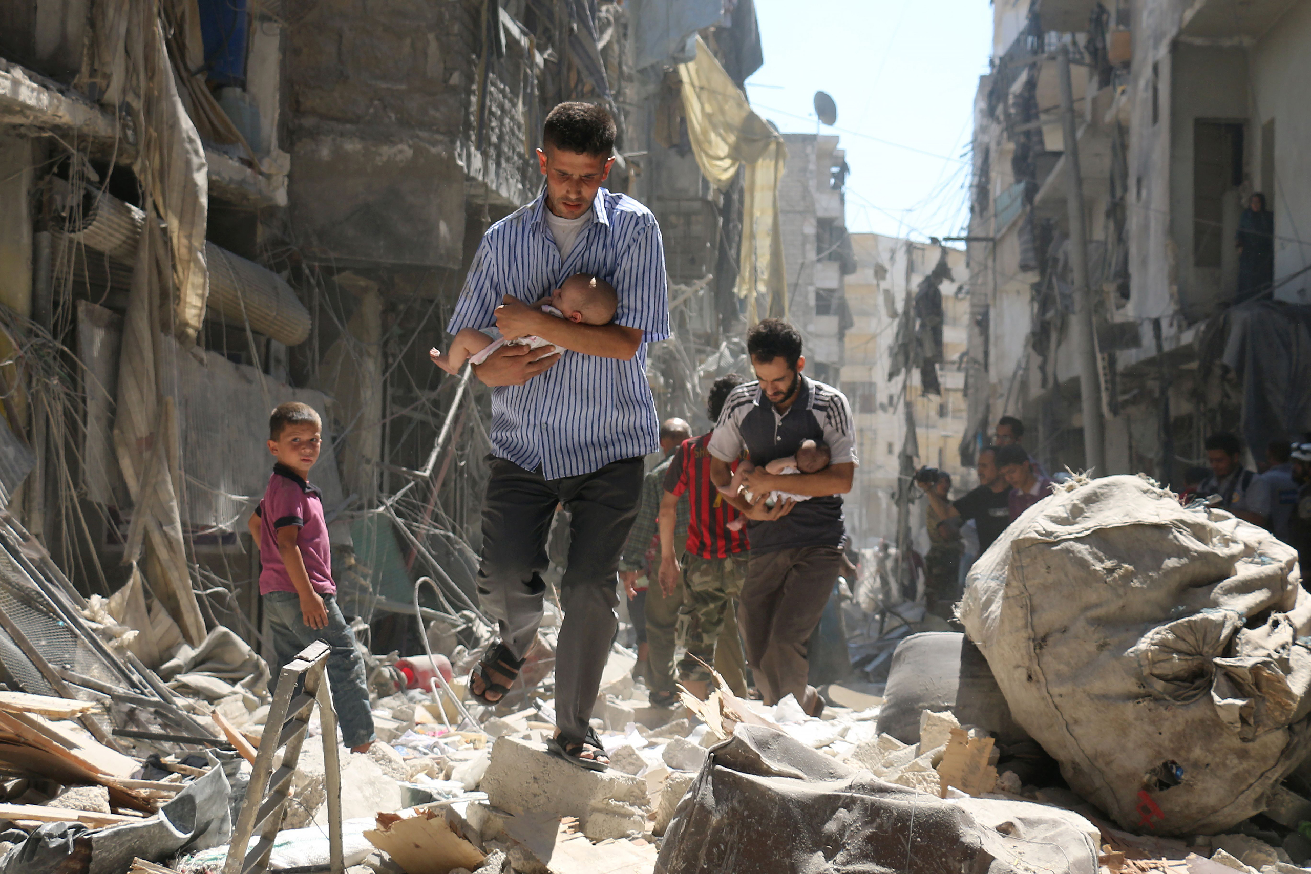 Syrian men carrying babies make their way through the rubble of destroyed buildings following a reported airstrike on the rebel-held Salihin neighborhood of Aleppo on Sept. 11, 2016.