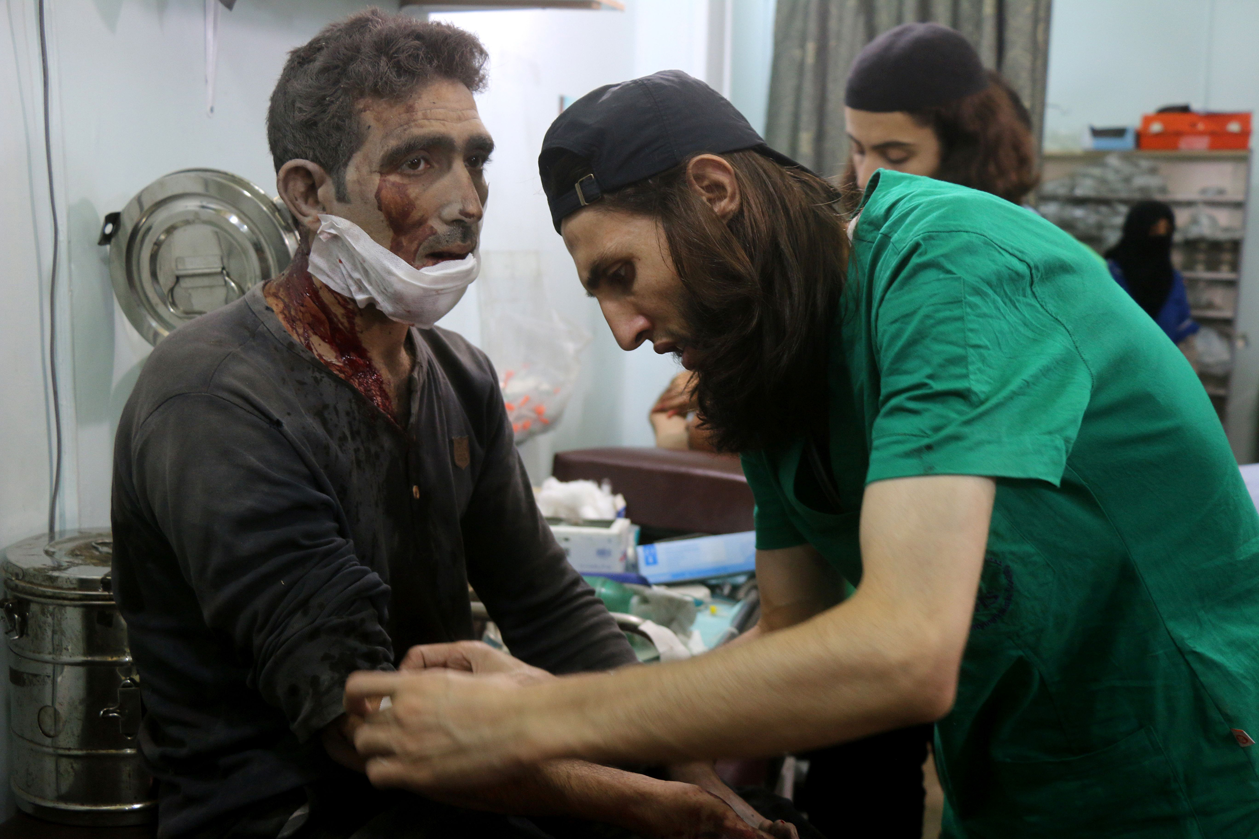 Syrian medics treat a man at a makeshift hospital in the Tariq al-Bab neighborhood of Aleppo after he was wounded during reported air raids that targeted rebel-held areas on Aug. 16, 2016.
