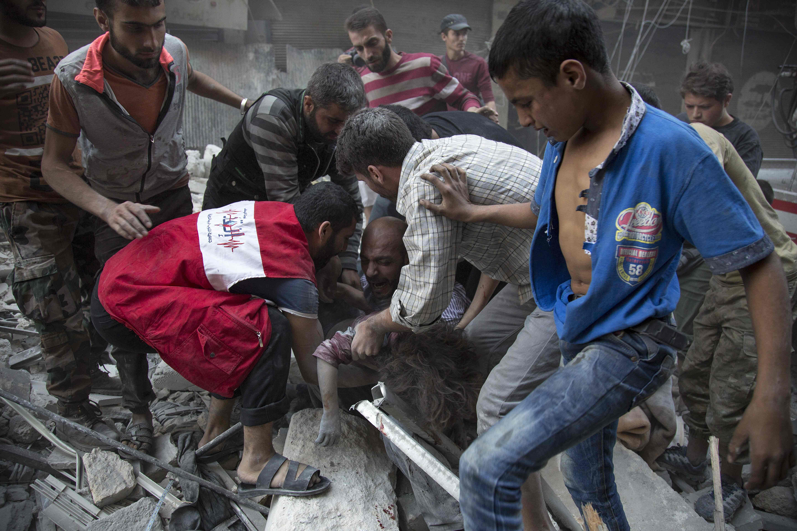 Syrians surround a man as he cries over the body of his child after she was pulled out from the rubble of a building following government airstrikes on a rebel-held neighborhood of Aleppo on Sept. 27, 2016.